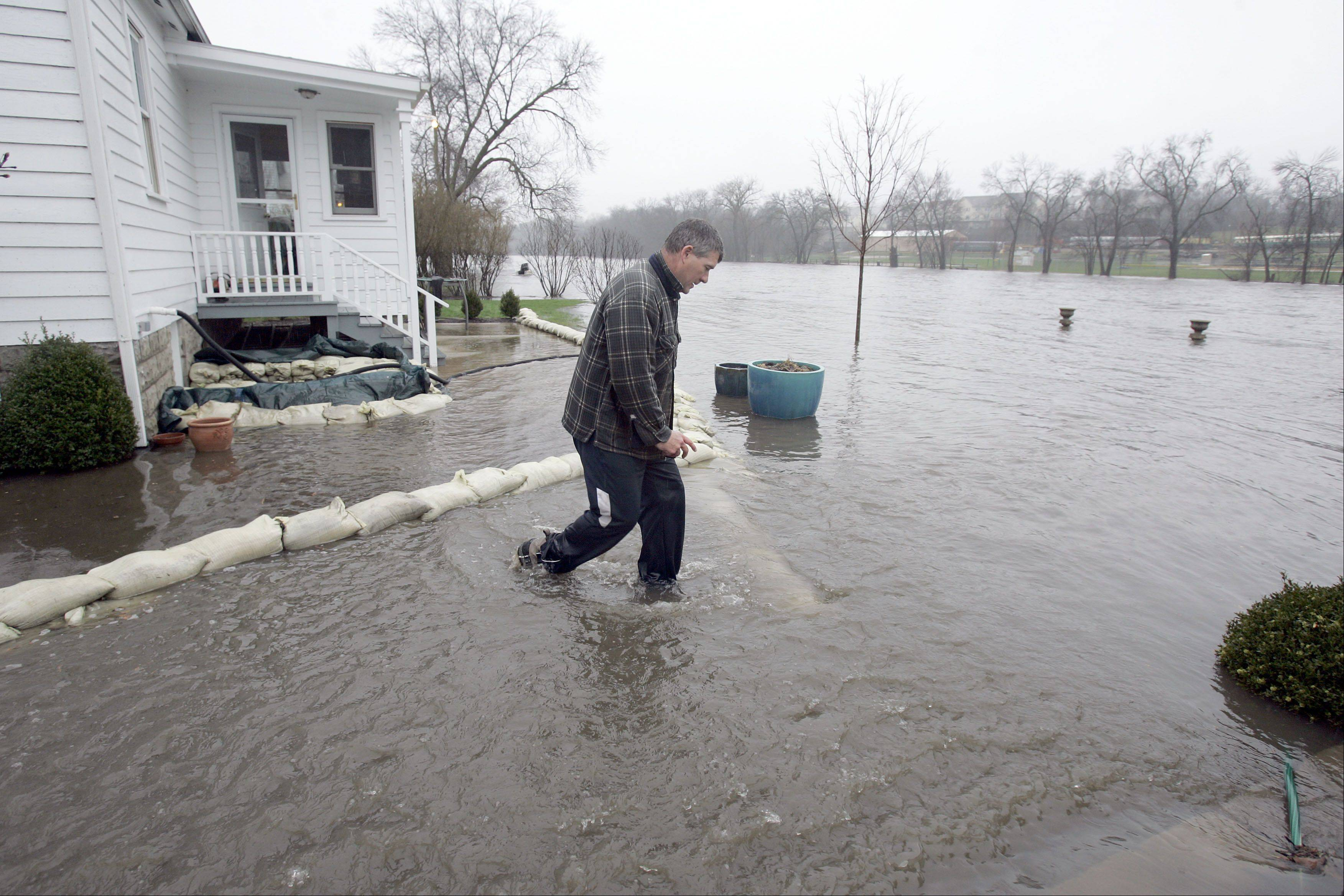 "Paul Gogo of South Elgin returns for another sandbag after flooding two months ago on the Fox River in South Elgin. ""This is just brutal, it's never been like this"" said Gogo, who had been up since the middle of the night April 18 working to protect his home on South River Street."