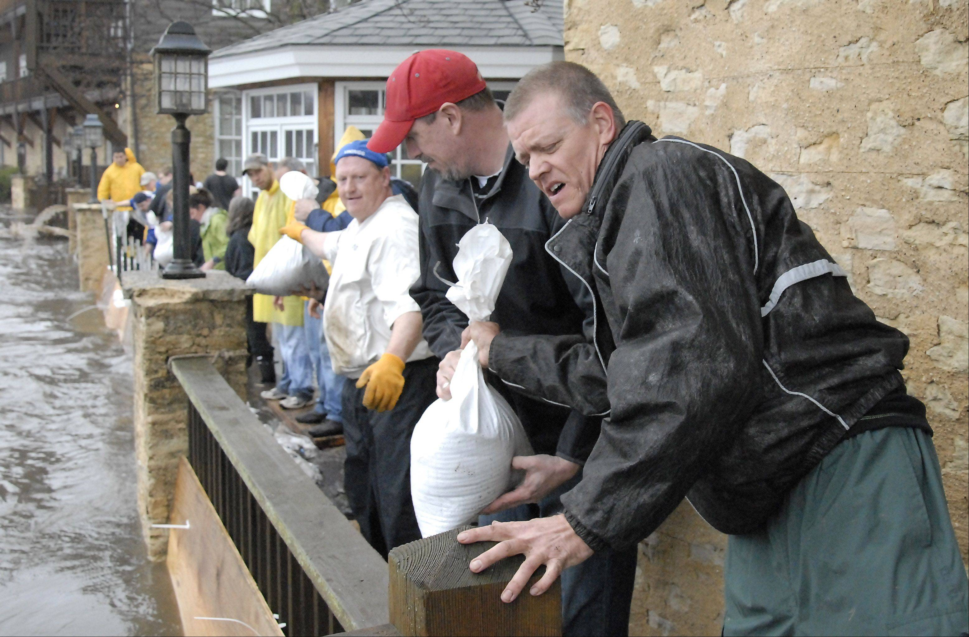 Volunteer sandbaggers Chris Schmedes of Geneva takes a bag from Brad Umholtz of South Elgin as they try to stop the Fox River from flooding the Herrington Inn April 18 in Geneva. Herrington owner Paul Ruby put out the call for help early and people came by the dozens to help out.