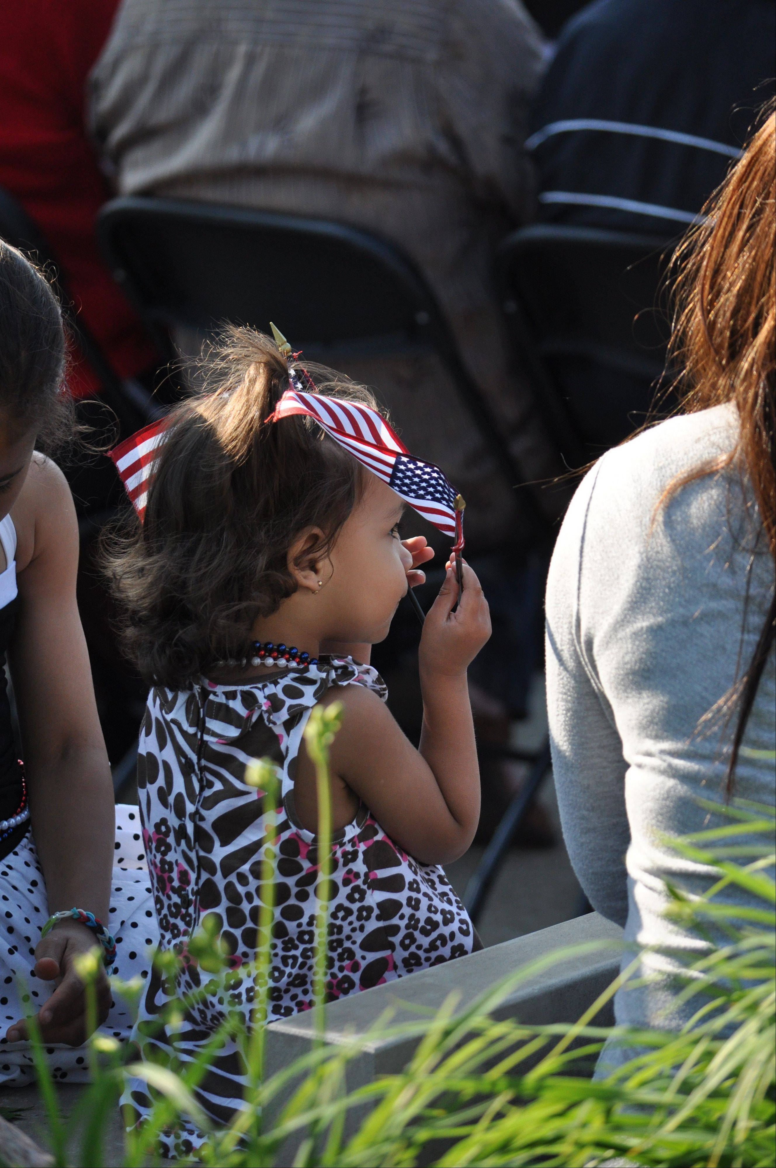 A girl holds miniature flags at the Flag Day ceremony Friday at Buffalo Grove Park District's Veterans Park, 1300 N. Weiland Road.