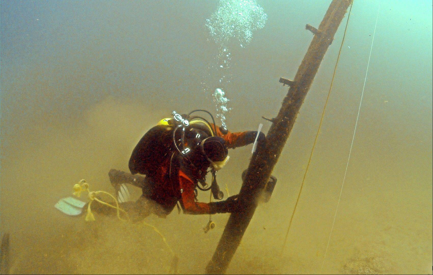 Diver Jim Nowka of Great Lakes Exploration Group inspects a wooden beam extending from the floor of Lake Michigan that experts believe may be part of the Griffin, a ship that sank in 1679. Crews are digging a pit at the base of the beam to see if it's attached to a buried ship.
