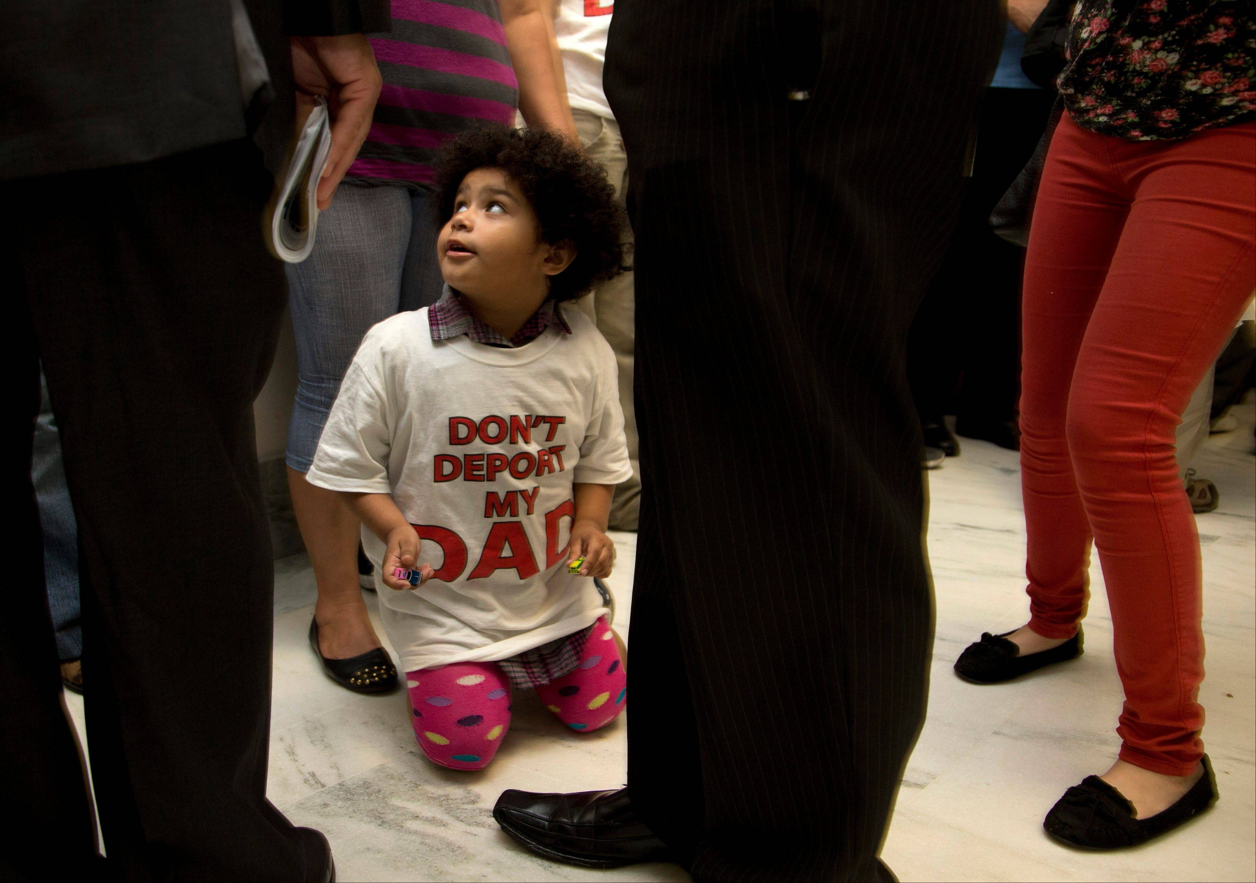 "Jackelin Alfaro, 4, in a T-shirt that reads ""Don't Deport my Dad"" sits in the hall with family members outside the House Judiciary Committee hearing on Capitol Hill in Washington, Tuesday, June 18, 2013. The committee hearing will discuss the Strengthen and Fortify Enforcement Act. The committee in the Republican-led House is preparing to cast its first votes on immigration this year, on a tough enforcement-focused measure that Democrats and immigrant groups are protesting loudly."
