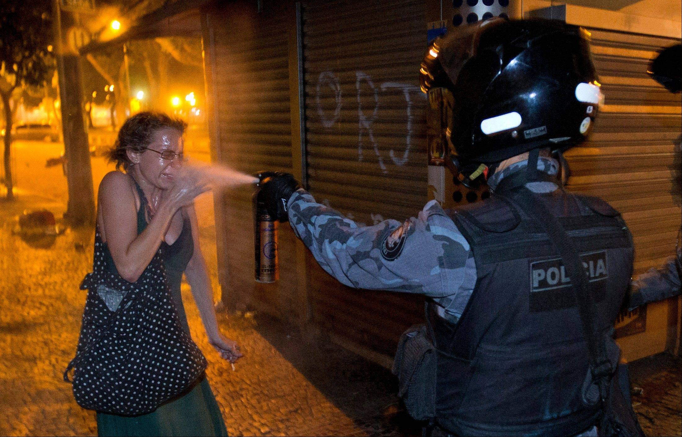 A military police officer uses pepper spray on a protester during a demonstration in Rio de Janeiro, Brazil, Monday, June 17, 2013. Protesters massed in Brazilian cities Monday for another round of demonstrations voicing disgruntlement about life in the country.