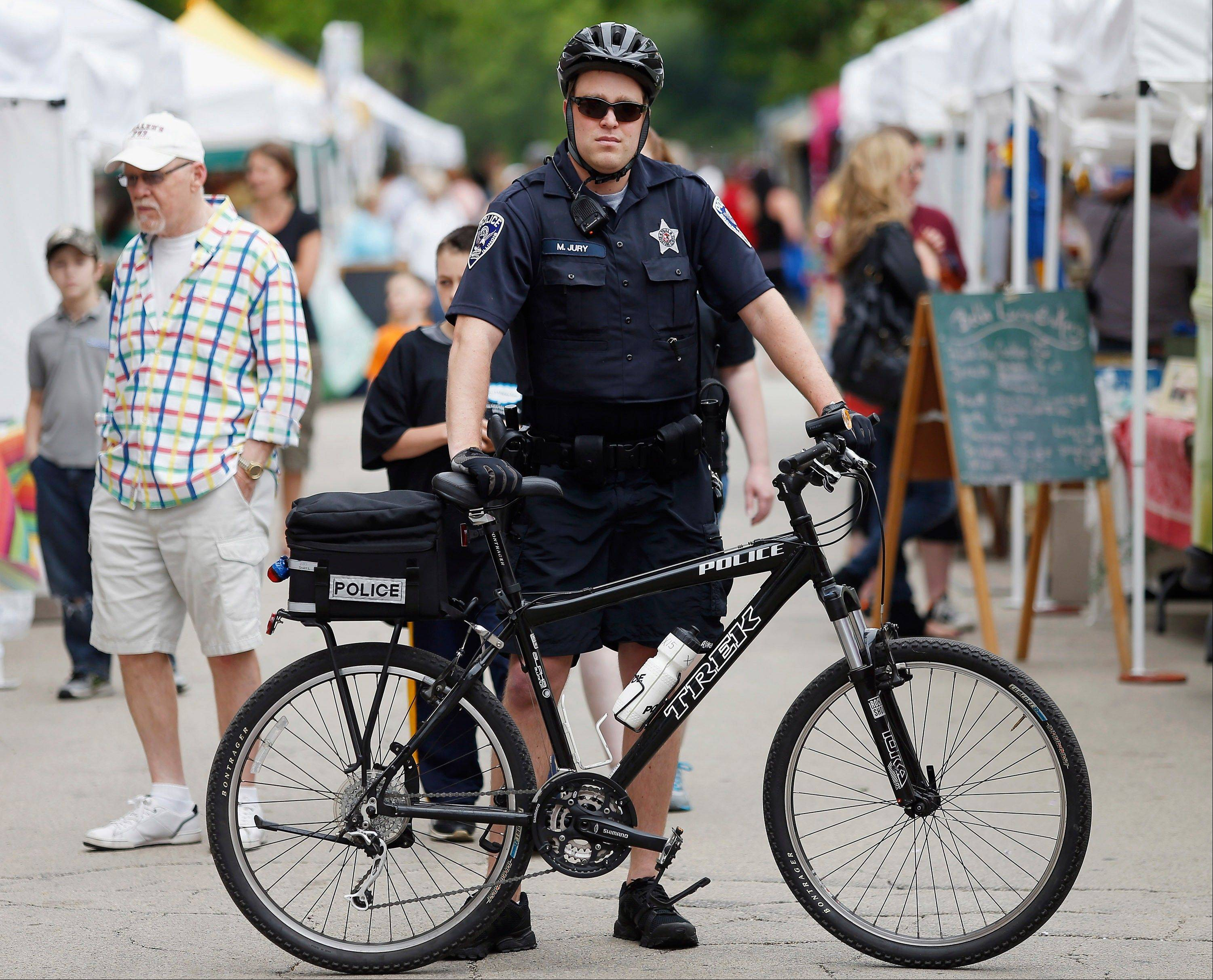 Associated PressRockford Police Officer Mike Jury stands with his bike at the entrance of the City Market in downtown Rockford.