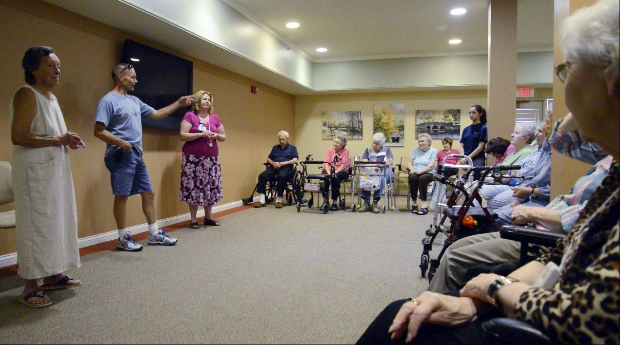 First Sgt. Jim Hicks speaks Monday afternoon to residents of Delnor Glen in St. Charles. Hicks' mother, Linda, right, works at the assisted living facility, and the residents have been sending care packages to his Afghanistan-based unit.