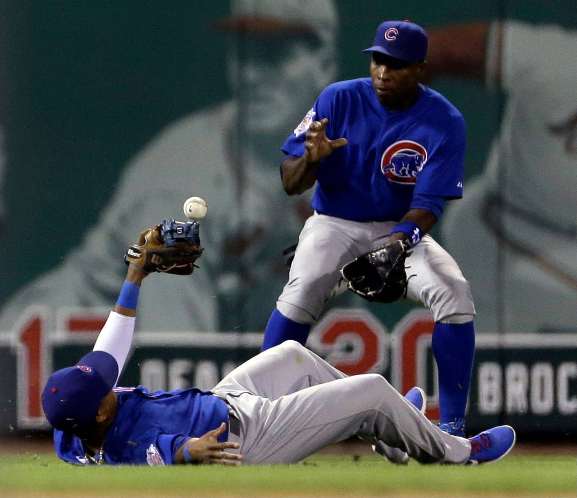 Chicago Cubs shortstop Starlin Castro, bottom, misses a ball hit by St. Louis Cardinals' Matt Holliday for a single as Cubs left fielder Alfonso Soriano watches during the ninth inning of a baseball game on Tuesday, June 18, 2013, in St. Louis.