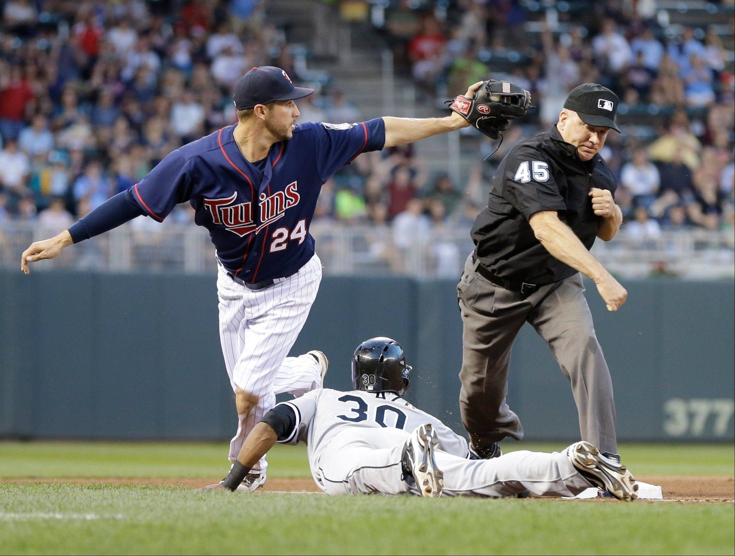 Third base umpire John Tumpane, right, calls the out on Chicago White Sox' Alejandro De Aza who was picked off third by Minnesota Twins third baseman Trevor Plouffe Tuesday night in Minneapolis.