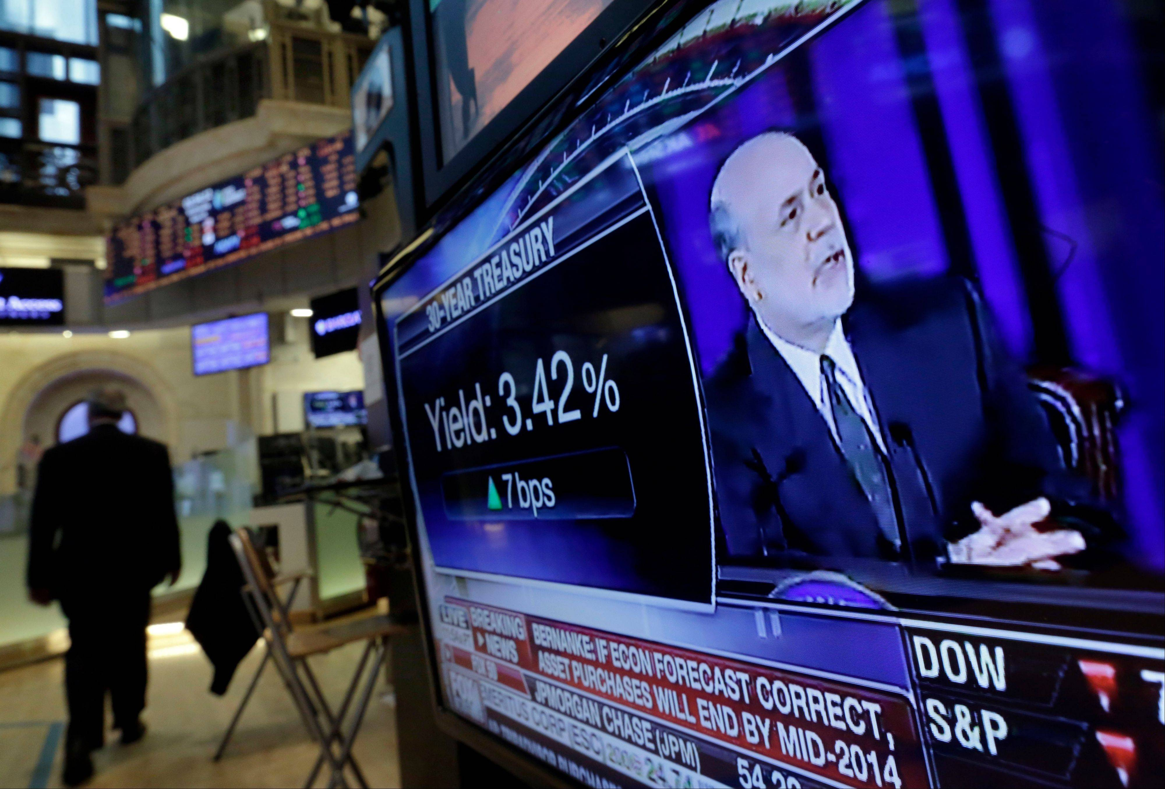 Fed Chairman Ben Bernanke�s news conference is on a television screen on the floor of the New York Stock Exchange Wednesday, when the Fed hinted it�s moving closer to slowing its bond-buying program, which is intended to keep long-term interest rates at record lows.