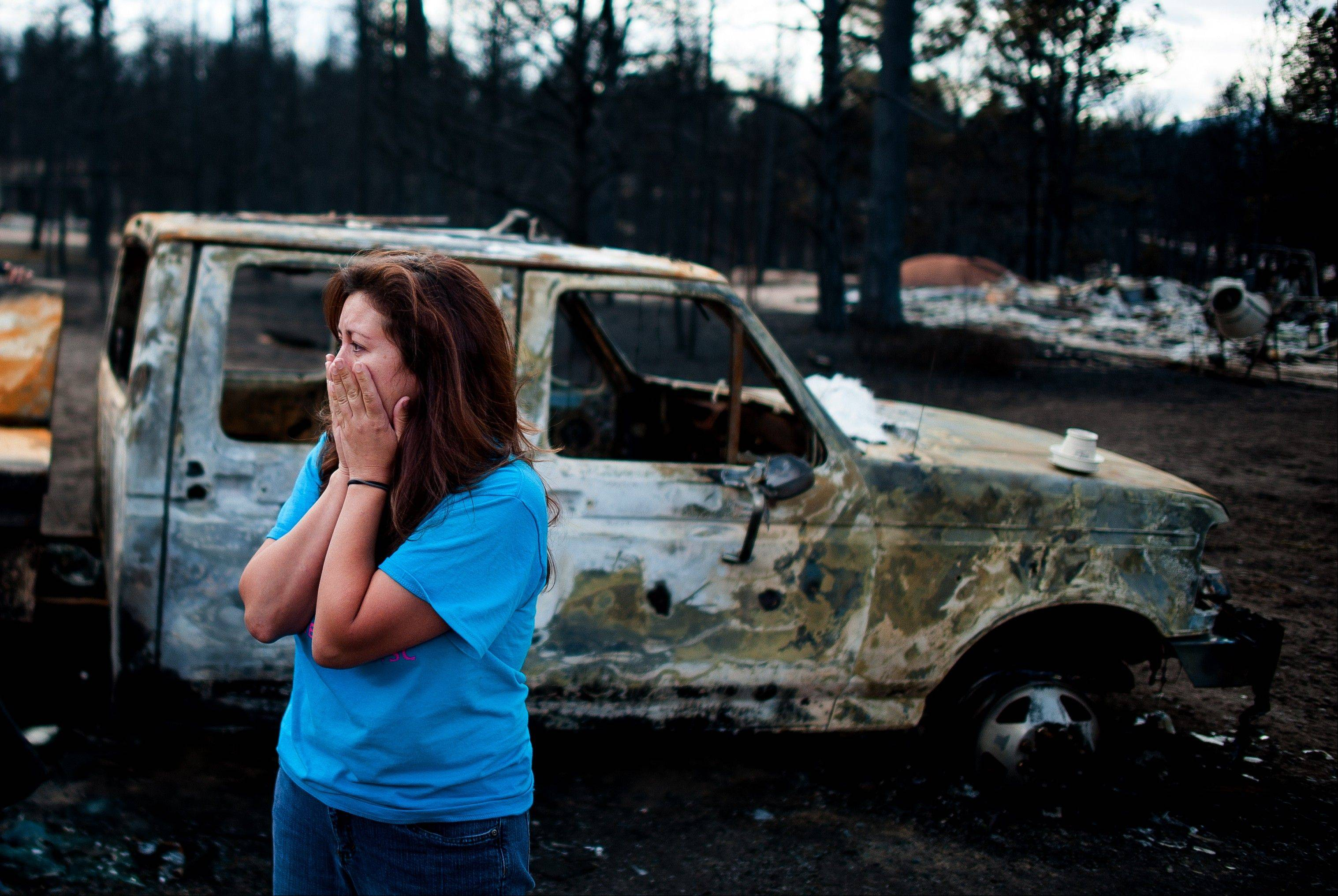 Bonnie Kruse reacts as she views her family's property that was in the path of the Black Forest Fire, Tuesday, June 18, 2013, in Colorado Springs, Colo. Of the six homes that Kruse and her family have in Black Forest, all but one was destroyed. The Black Forest Fire, the most destructive wildfire in Colorado history, has destroyed 502 homes and charred more than 22 square miles. It was 85 percent contained Tuesday.