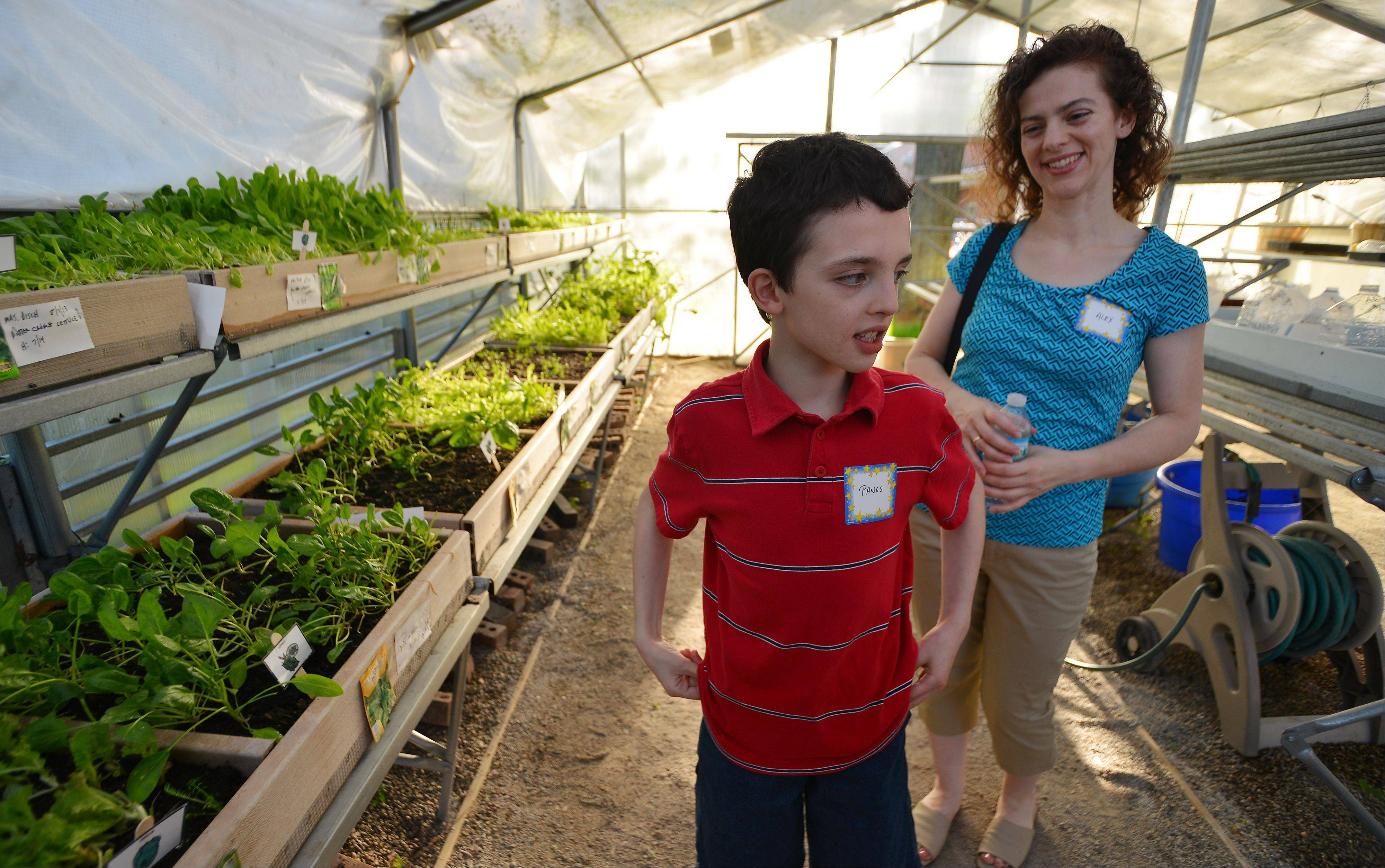 "Panos Calderaro, 10, of Arlington Heights takes a tour of the greenhouse with his mom Alex as part of the recognition event for Northwest Suburban Special Education Organization's ""Shining Stars"" at Miner School in Arlington Heights."
