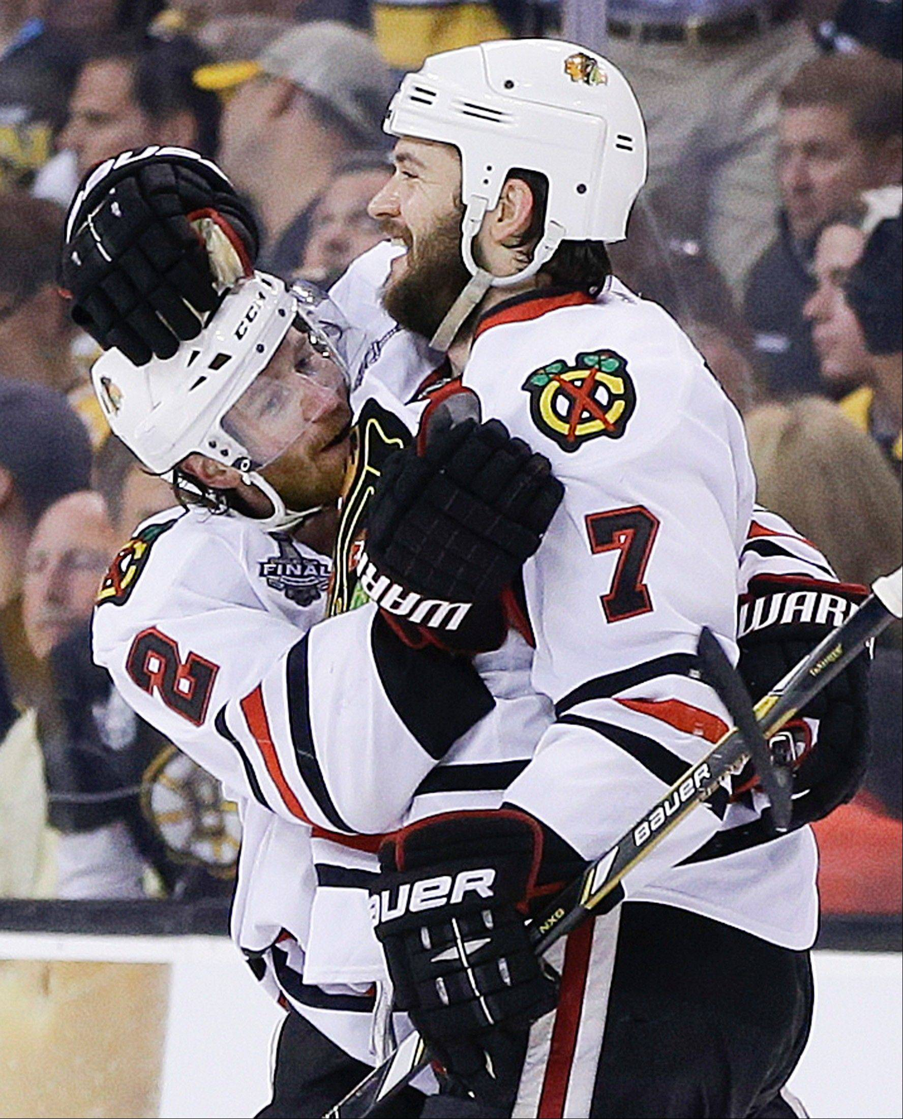 Blackhawks defenseman Brent Seabrook (7) celebrates his game-winning goal against the Boston Bruins with defenseman Duncan Keith (2) during Game 4 of the NHL hockey Stanley Cup Finals Wednesday in Boston. Chicago won 6-5.