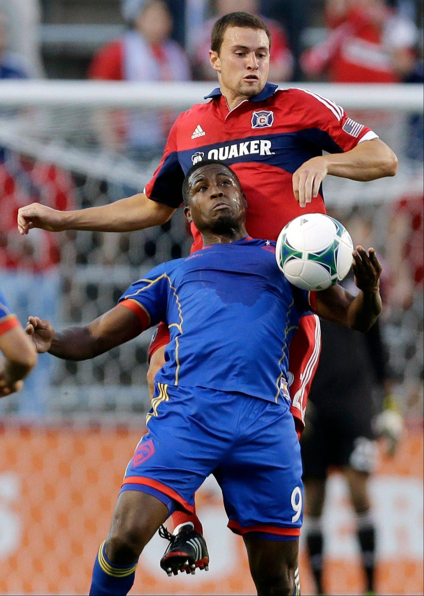 Colorado Rapids forward Edson Buddle, bottom, and Chicago Fire defender Austin Berry battle for the ball during the first half of an MLS soccer match Wednesday night.