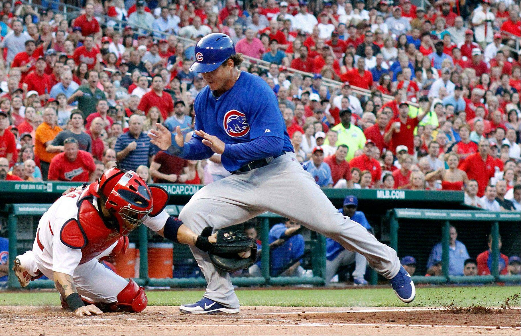 The Cubs' Anthony Rizzo is tagged by Cardinals catcher Yadier Molina — but he manages to knock the ball loose and score during Wednesday's game at Busch Stadium in St. Louis.