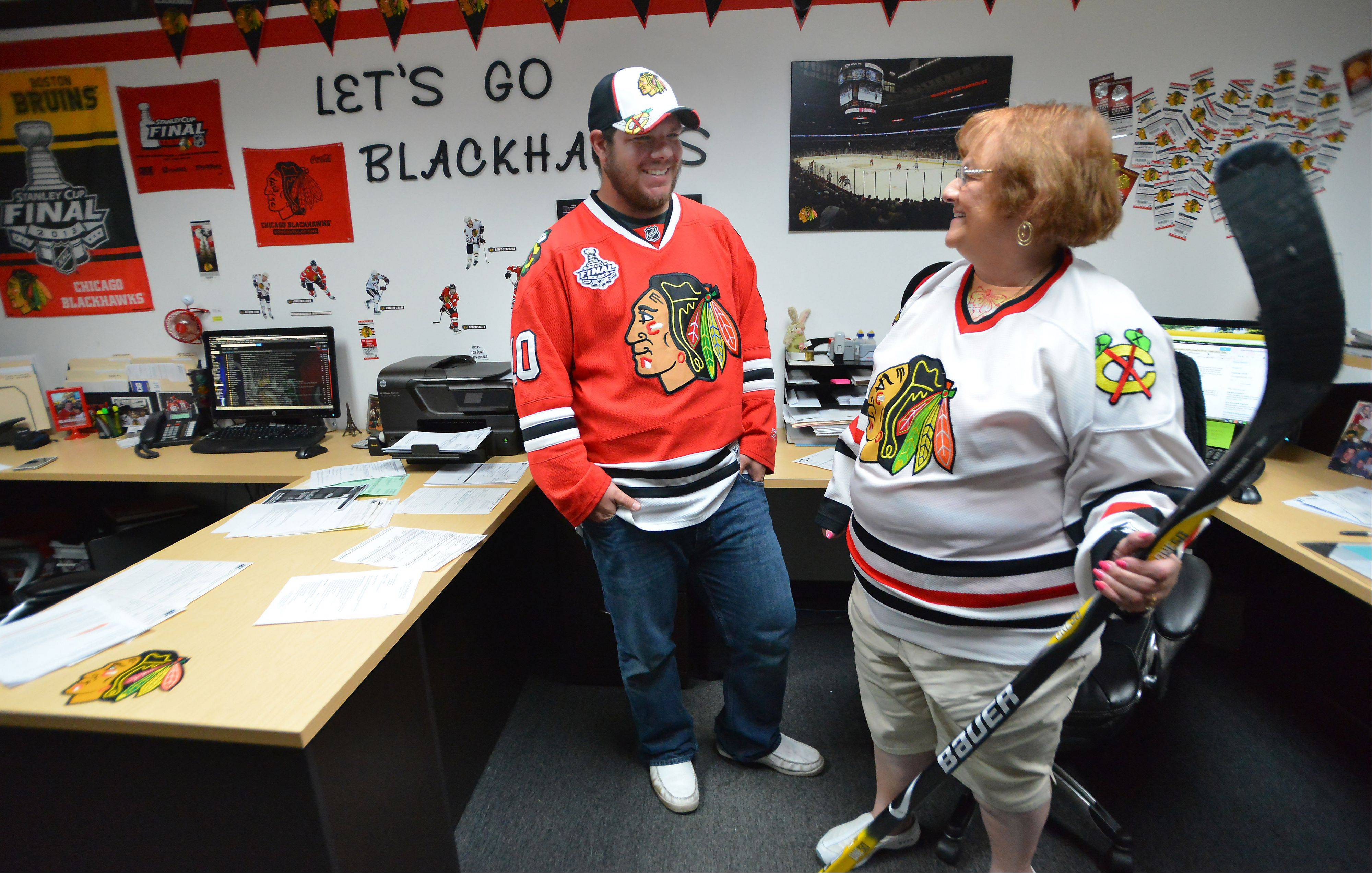 Bille Marcum and his grandmother, Sandy, stand in their Chicago Blackhawks-themed office at Pro-Tech Roofing Co. in Des Plaines. The Marcum family converted the office into a shrine for their beloved Chicago Blackhawks.