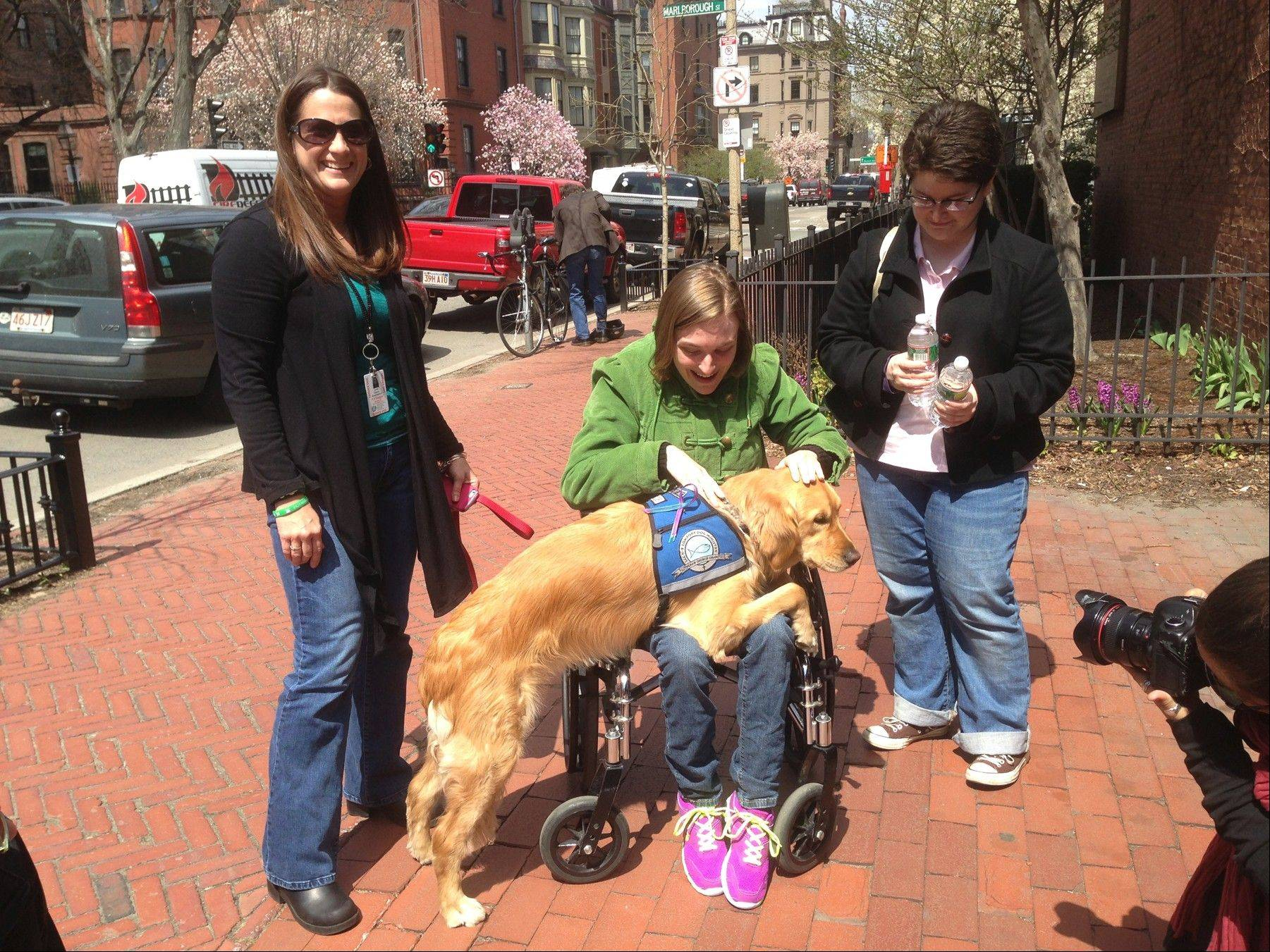 Handler Deana Mastropietro and K-9 Maggie visit with residents on the streets of Boson.