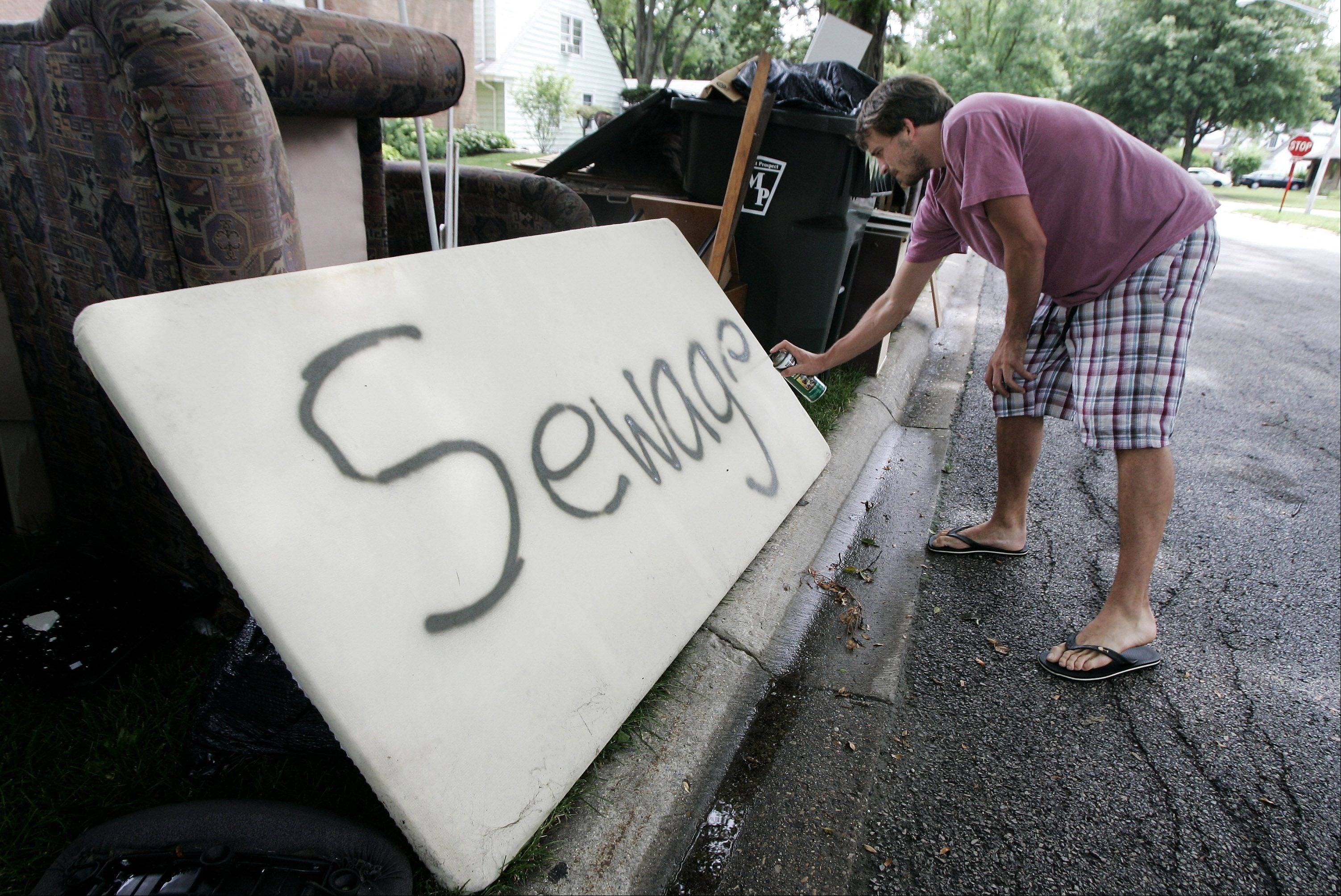 This is an example of the damage wrought by flooding in the July 23, 2011, storm. Robert Zapfel spray-painted a sign to warn scavengers away from sewage-contaminated furniture he left alongside the road of his Mount Prospect residence on Emerson Street.