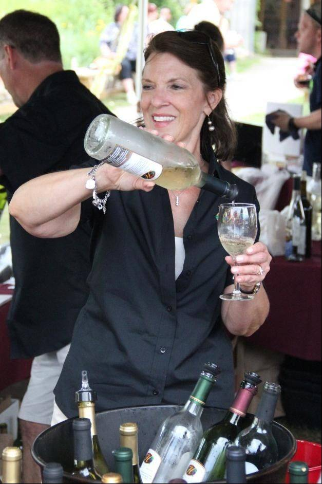 A representative from Hailey's Winery pours wine for a Solstice Hop and Vine Fest guest.