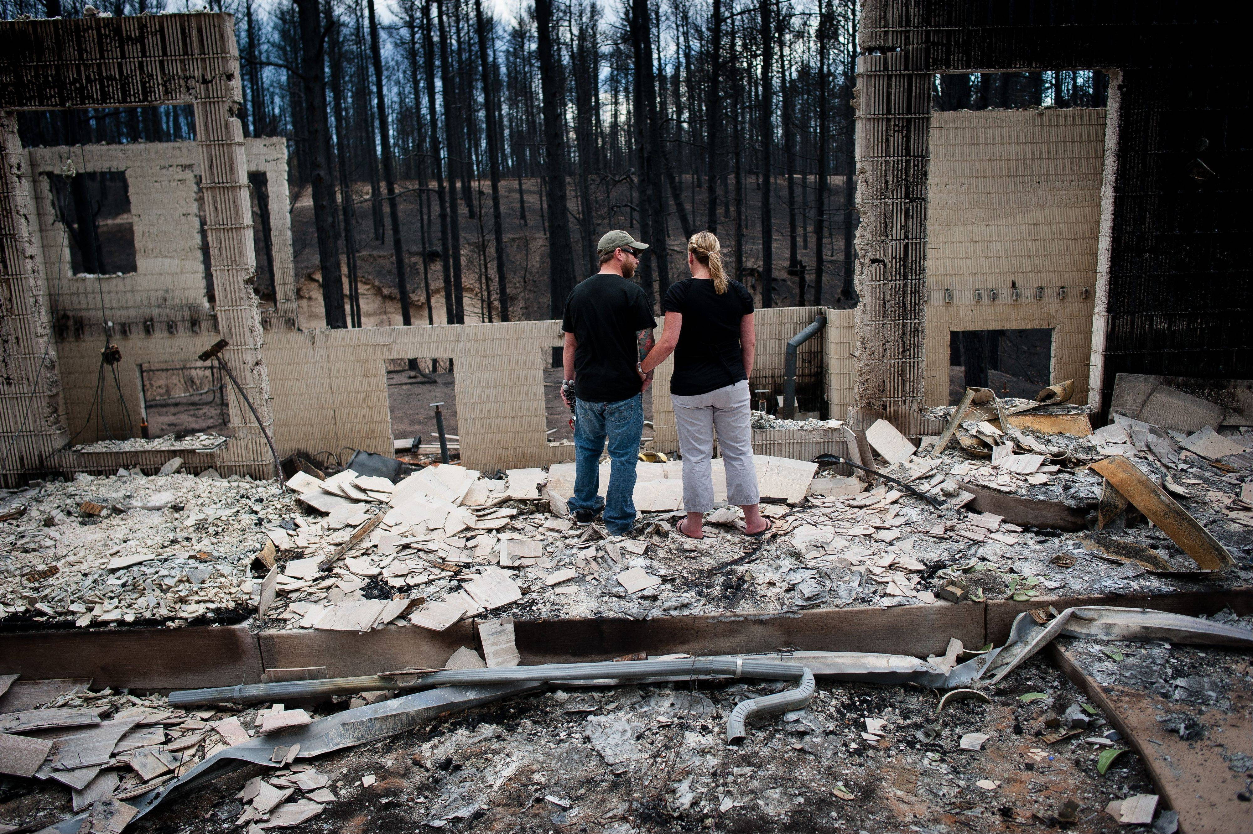 Jeremy and Kelly Beach look into the remains of their home off Ravine Drive, Tuesday, June 18, 2013, in Colorado Springs, Colo. Residents were allowed back into the area for a short period of time to view the properties that sustained the most damage from the fire. The Black Forest Fire, the most destructive wildfire in Colorado history, has destroyed 502 homes and charred more than 22 square miles. It was 85 percent contained Tuesday.