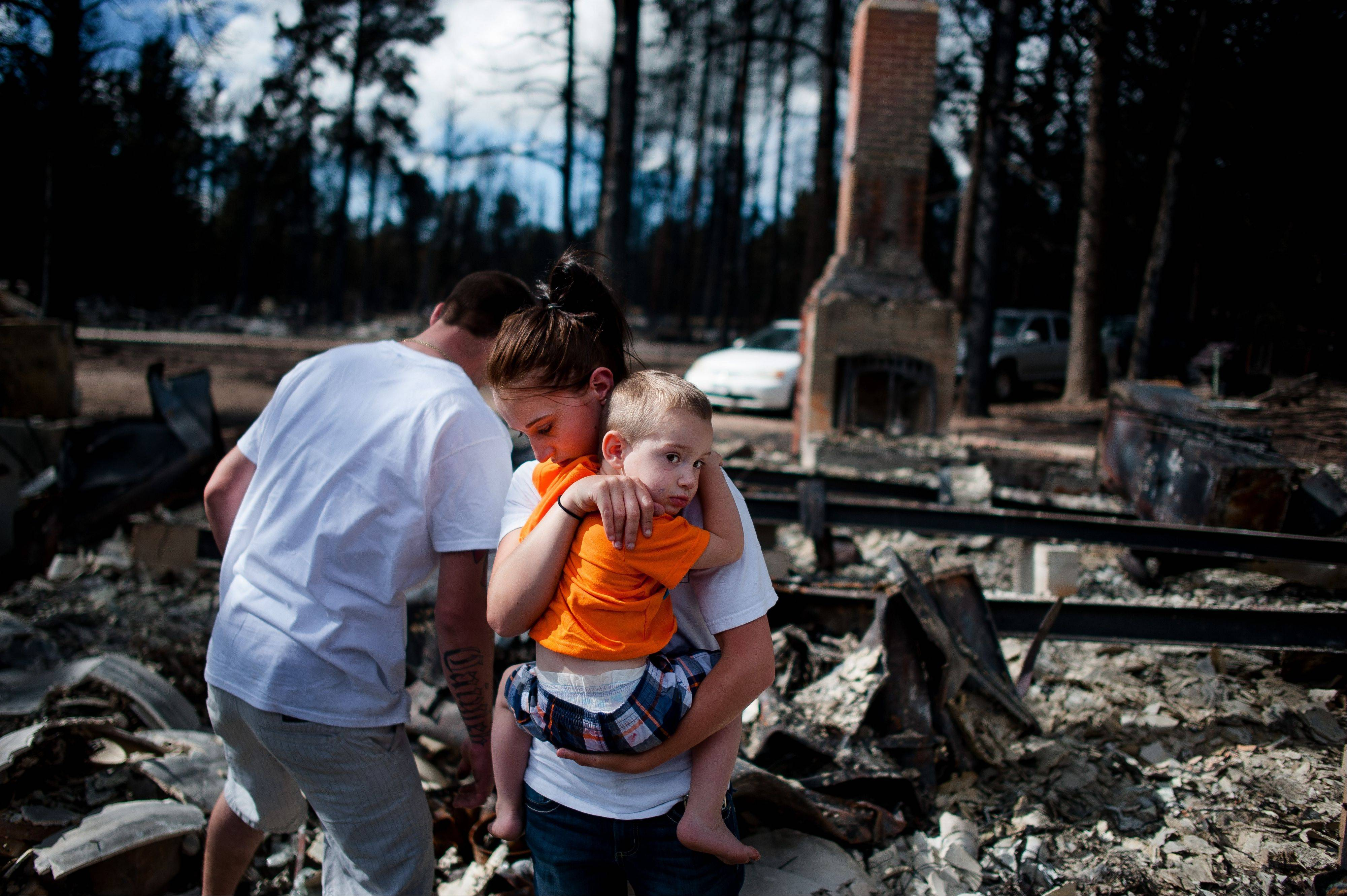 Brandy Burton carries her son Caiyleb Lewis, 2, through the rubble of her family's home that was completely destroyed in the Black Forest Fire, Tuesday, June 18, 2013, in Colorado Springs, Colo. Residents were allowed back into the area for a short period of time to view the properties that sustained the most damage from the fire. The Black Forest Fire, the most destructive wildfire in Colorado history, has destroyed 502 homes and charred more than 22 square miles. It was 85 percent contained Tuesday.