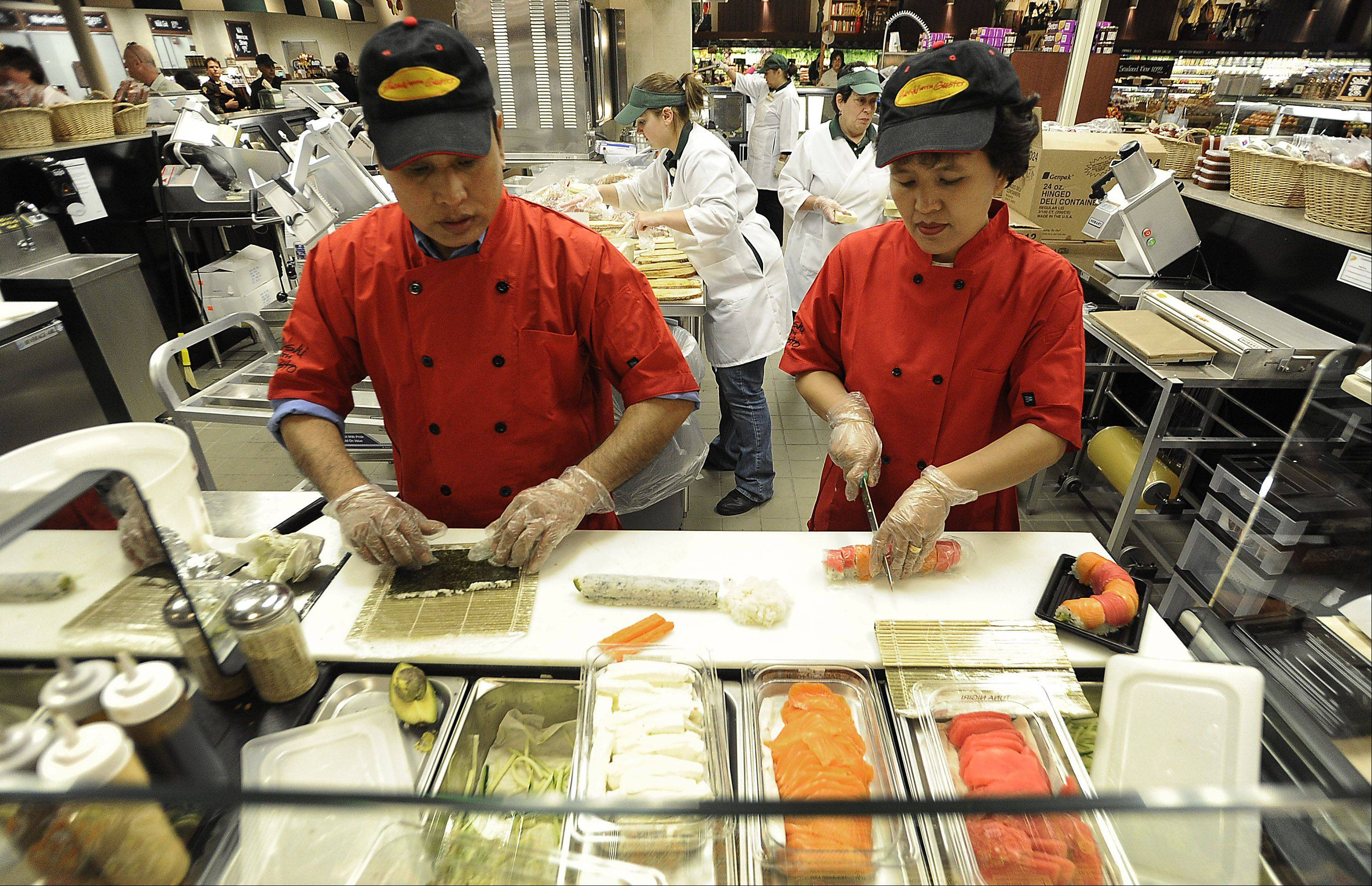Brother and sister Za Cung and Ngun Hliang of Northbrook prepare fresh Sushi for the shoppers at The Fresh Market in Lincolnshire during the store's grand opening on Wednesday.