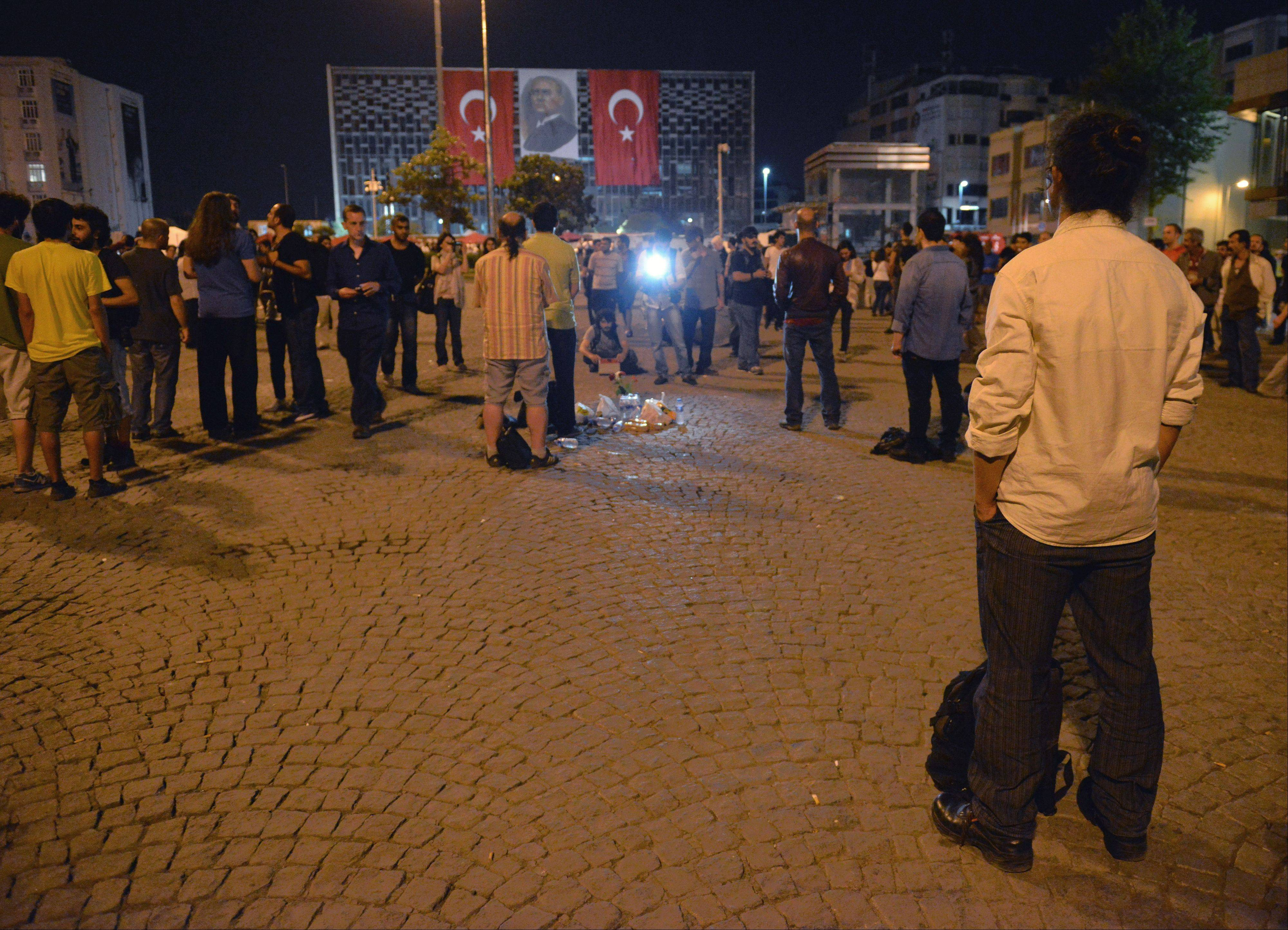 Erdem Gunduz, right, stands silently on Taksim Square in Istanbul, Turkey, early Tuesday, June 18, 2013. After weeks of confrontation with police, sometimes violent, Turkish protesters are using a new form of resistance: standing silently. The development started late Monday when a solitary man began standing in passive defiance against Prime Minister Recep Tayyip Erdogan's authority at Istanbul's central Taksim Square. The square has been sealed off from mass protests since police cleared it over the weekend. The man has identified himself as Erdem Gunduz, a performance artist. His has sparked imitation by others and has provoked widespread comment on social media.