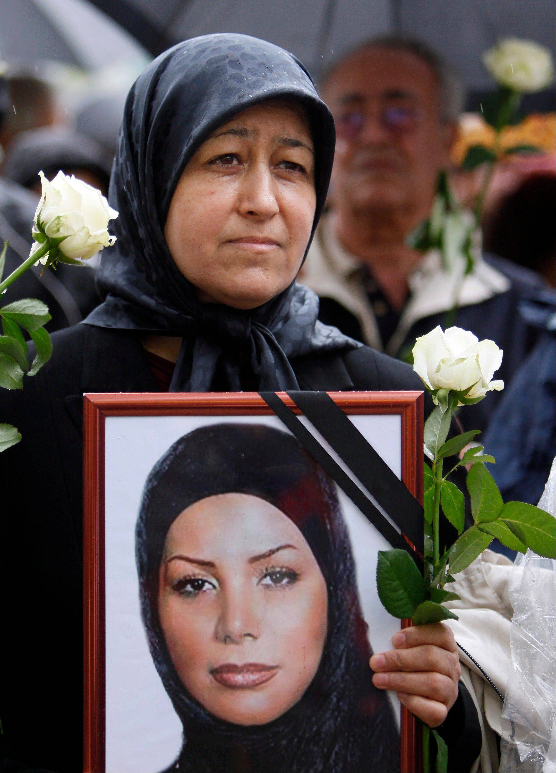 In this 2009 file photo, a woman protests against the political situation in Iran in Berlin. The protest was part of the Global Action Day 'United for Iran'. The photograph shows Iranian student Neda who was killed during a mass demonstration following the presidential elections in Iran.