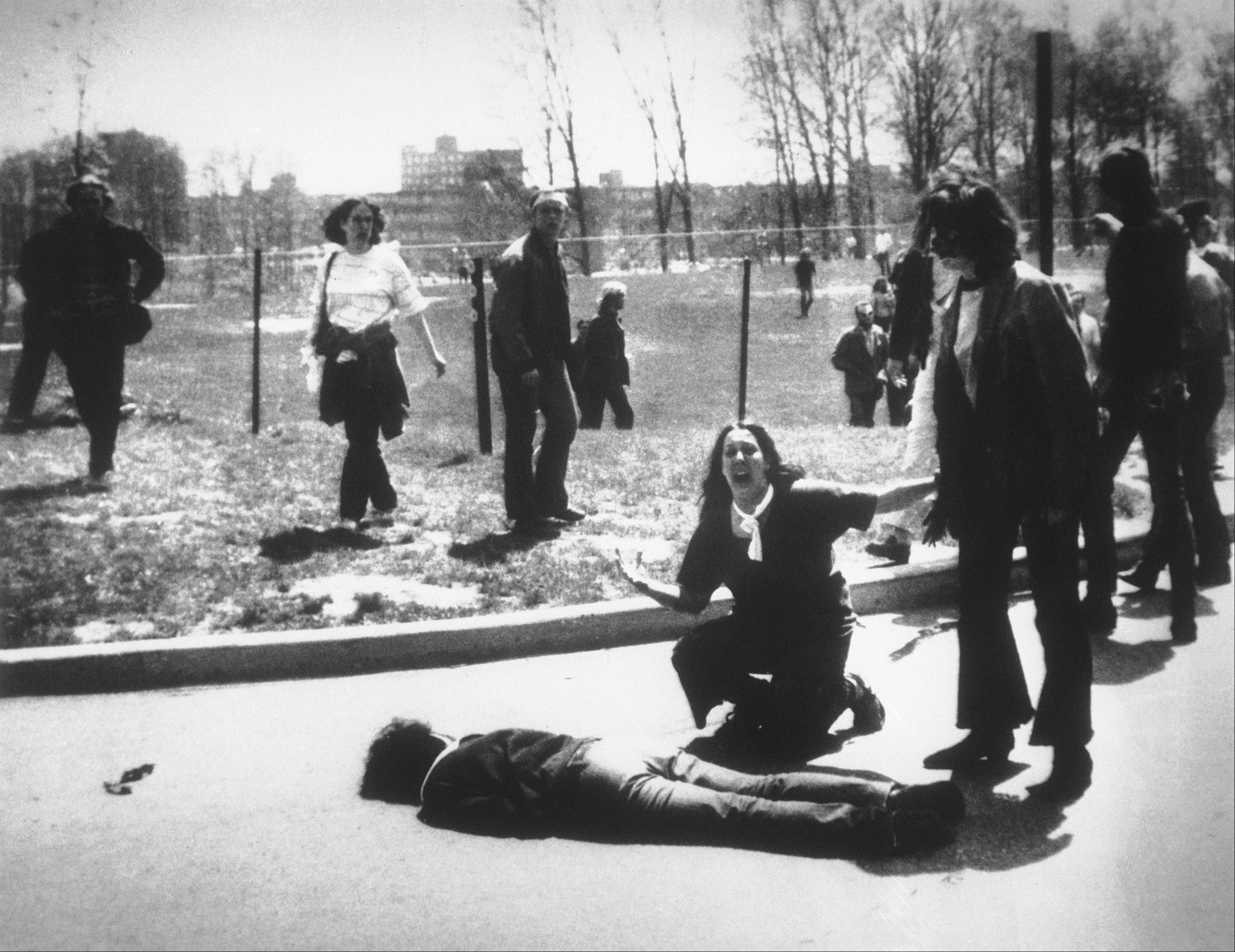 In this May 4, 1970, file photo, Mary Ann Vecchio gestures and screams as she kneels by the body of a student lying face down on the campus of Kent State University, Kent, Ohio. National Guardsmen had fired into a crowd of demonstrators, killing four.