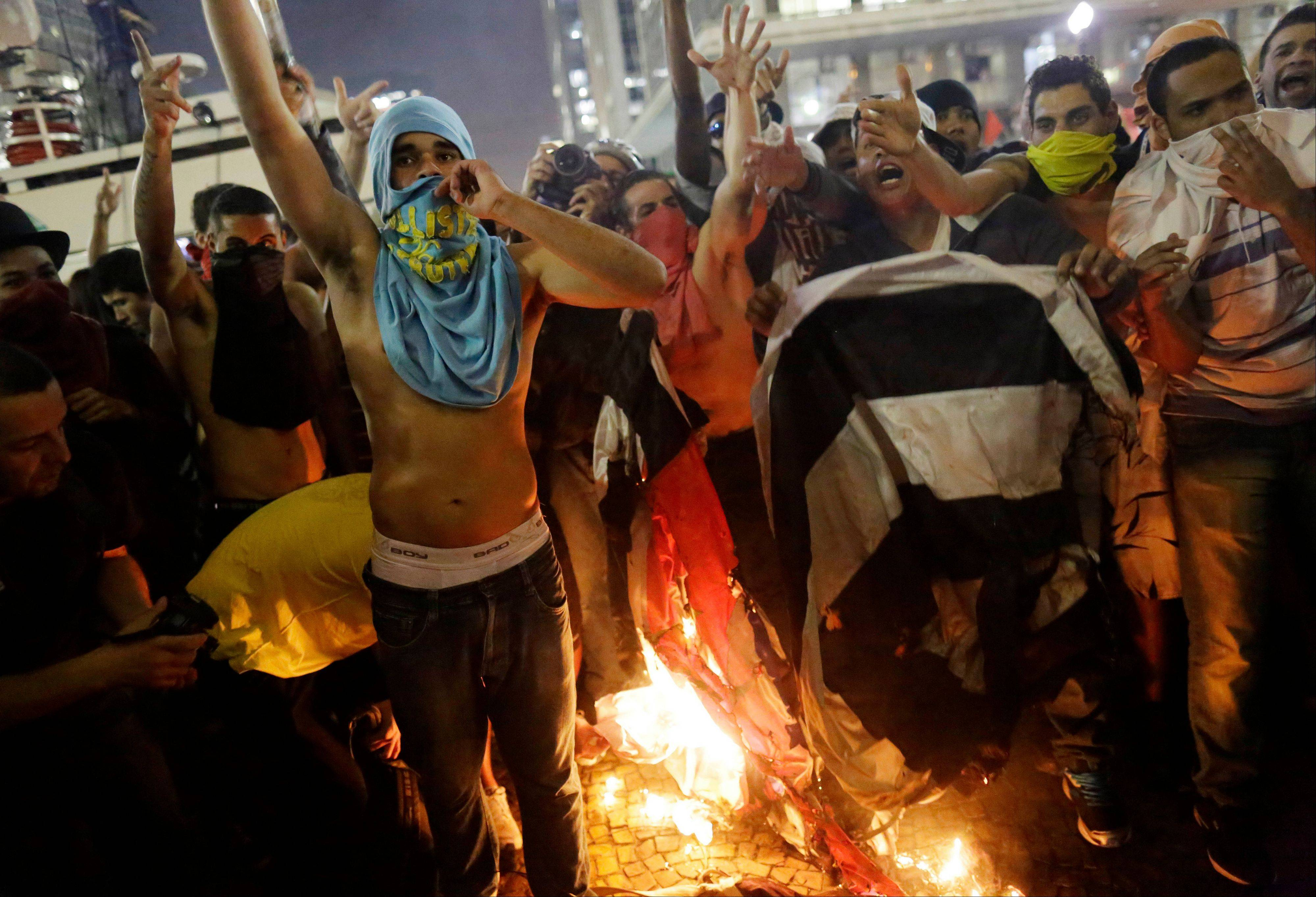 Protesters burn a Sao Paulo state flag in front of City Hall in Sao Paulo, Brazil, Tuesday. Some of the biggest demonstrations since the end of Brazil's 1964-85 dictatorship have broken out across this continent-sized country, uniting multitudes frustrated by poor transportation, health services, education and security despite a heavy tax burden.