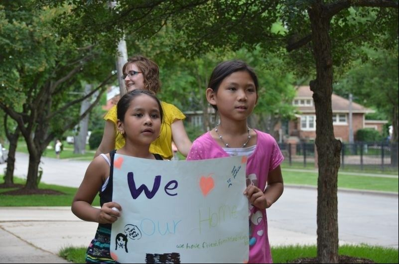 Residents of the Parkside Apartments, including children of refugees and immigrants, march together to the Glen Ellyn Civic Center Monday night to protest a proposed TIF district.