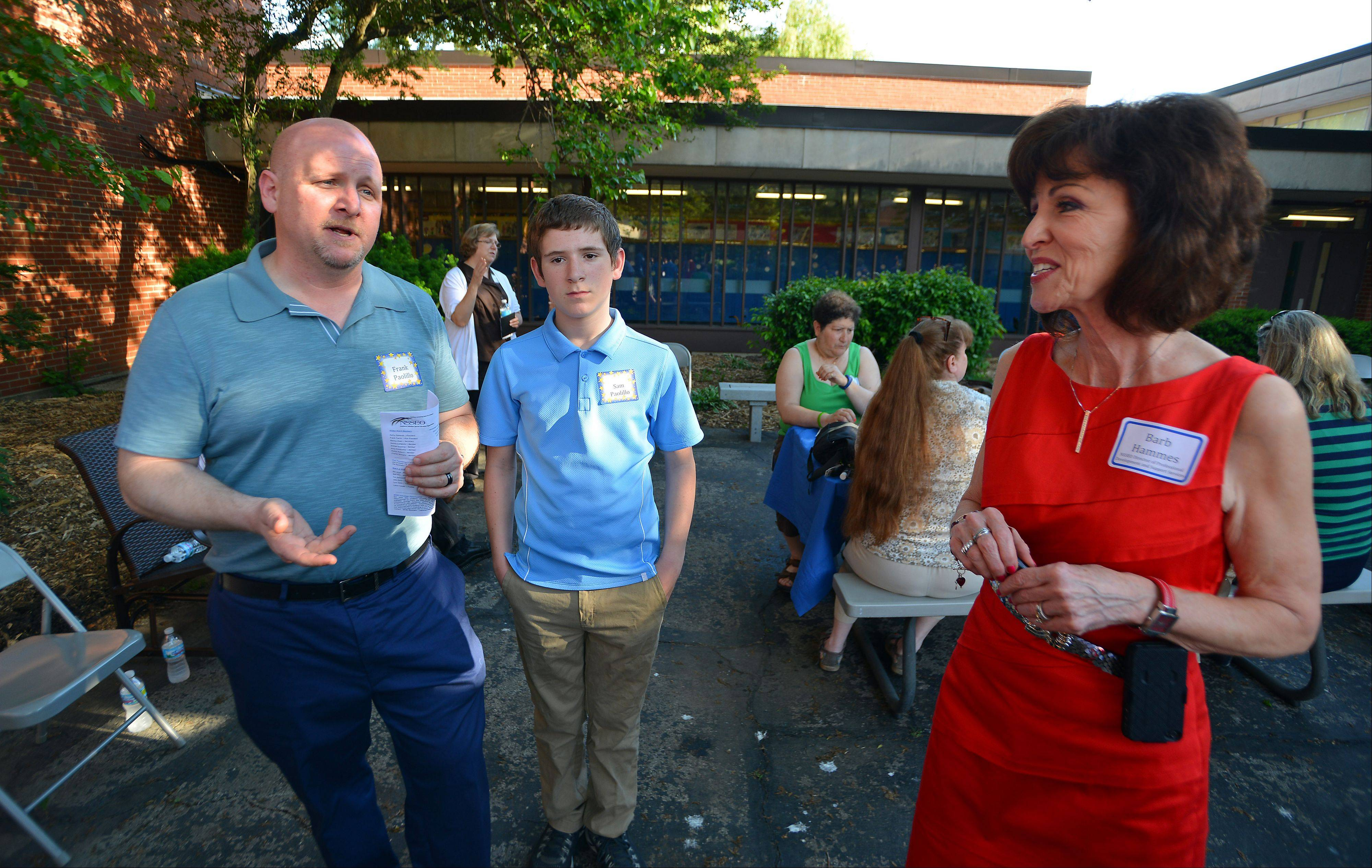 Barb Hammes, NSSEO director of professional development and support service, talks with Frank Paolillo and his son Sam, 13, of Park Ridge, who donated 20 iPads to Timberland School with Magellan Corp. in Deerfield.