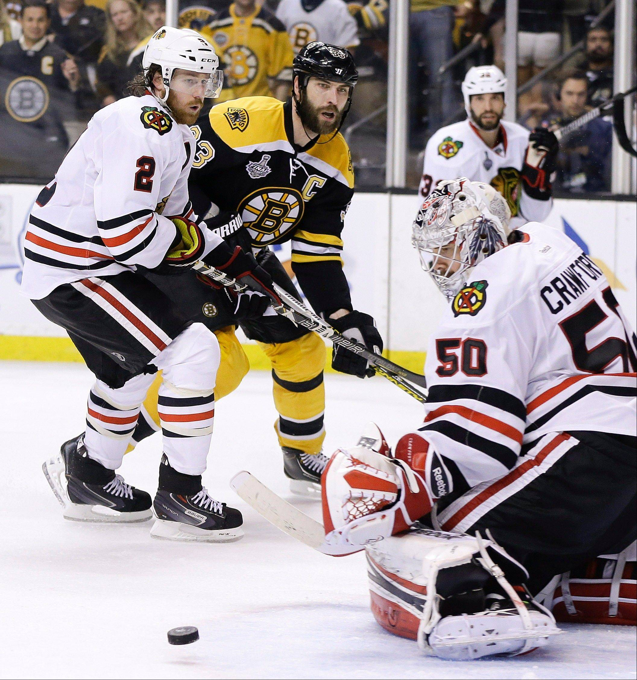 Chicago Blackhawks goalie Corey Crawford (50) turns the puck aside in front of Boston Bruins defenseman Zdeno Chara (33), of Slovakia, and Blackhawks defenseman Duncan Keith (2) during the second period in Game 4 of the NHL hockey Stanley Cup Finals.