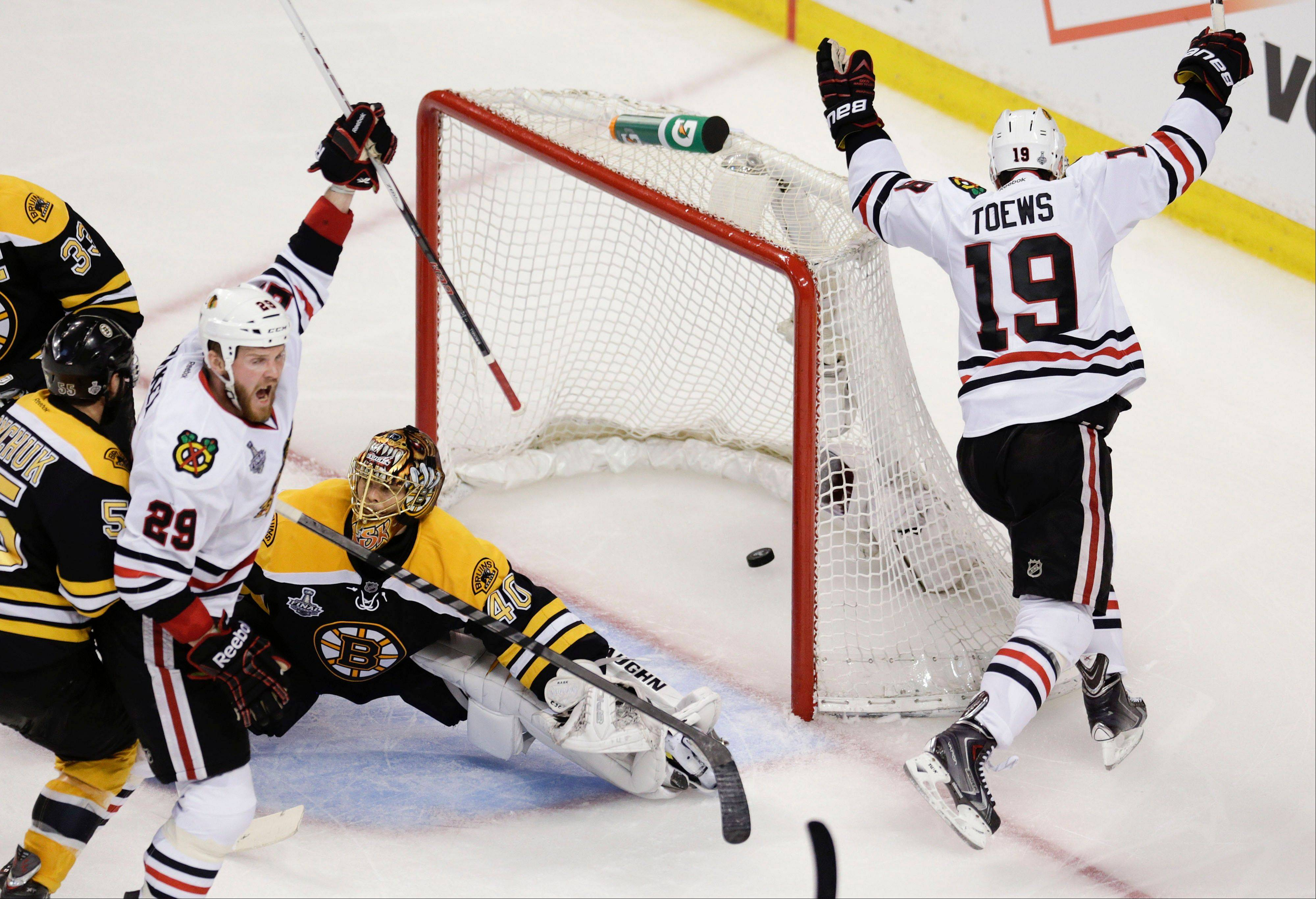 Chicago Blackhawks center Jonathan Toews (19) celebrates his goal against Boston Bruins goalie Tuukka Rask (40), of Finland, as Chicago Blackhawks left wing Bryan Bickell (29) joins the celebration during the second period in Game 4 of the NHL hockey Stanley Cup Finals.