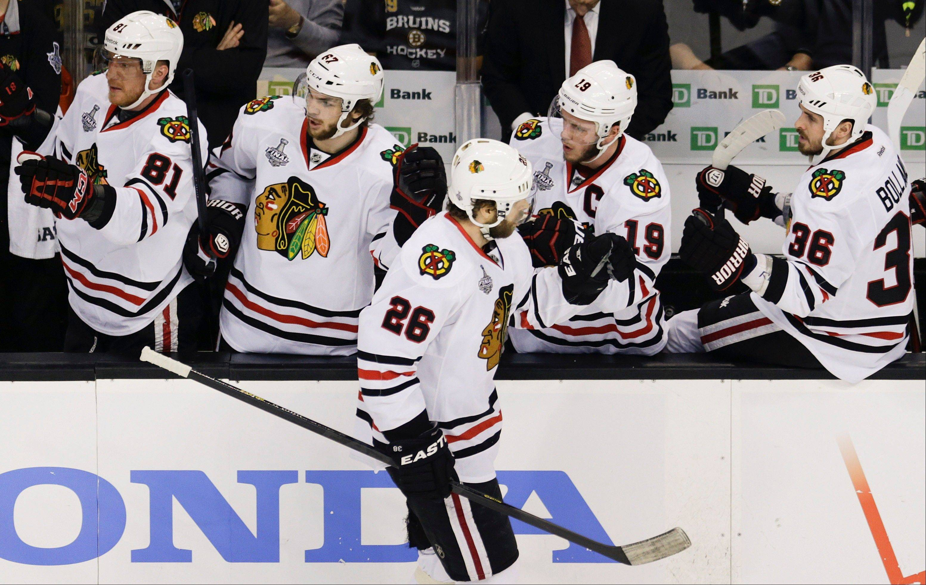 Chicago Blackhawks center Michal Handzus (26), of Slovakia, is congratulated by teammates on the bench after scoring against the Boston Bruins during the first period in Game 4 of the NHL hockey Stanley Cup Finals.