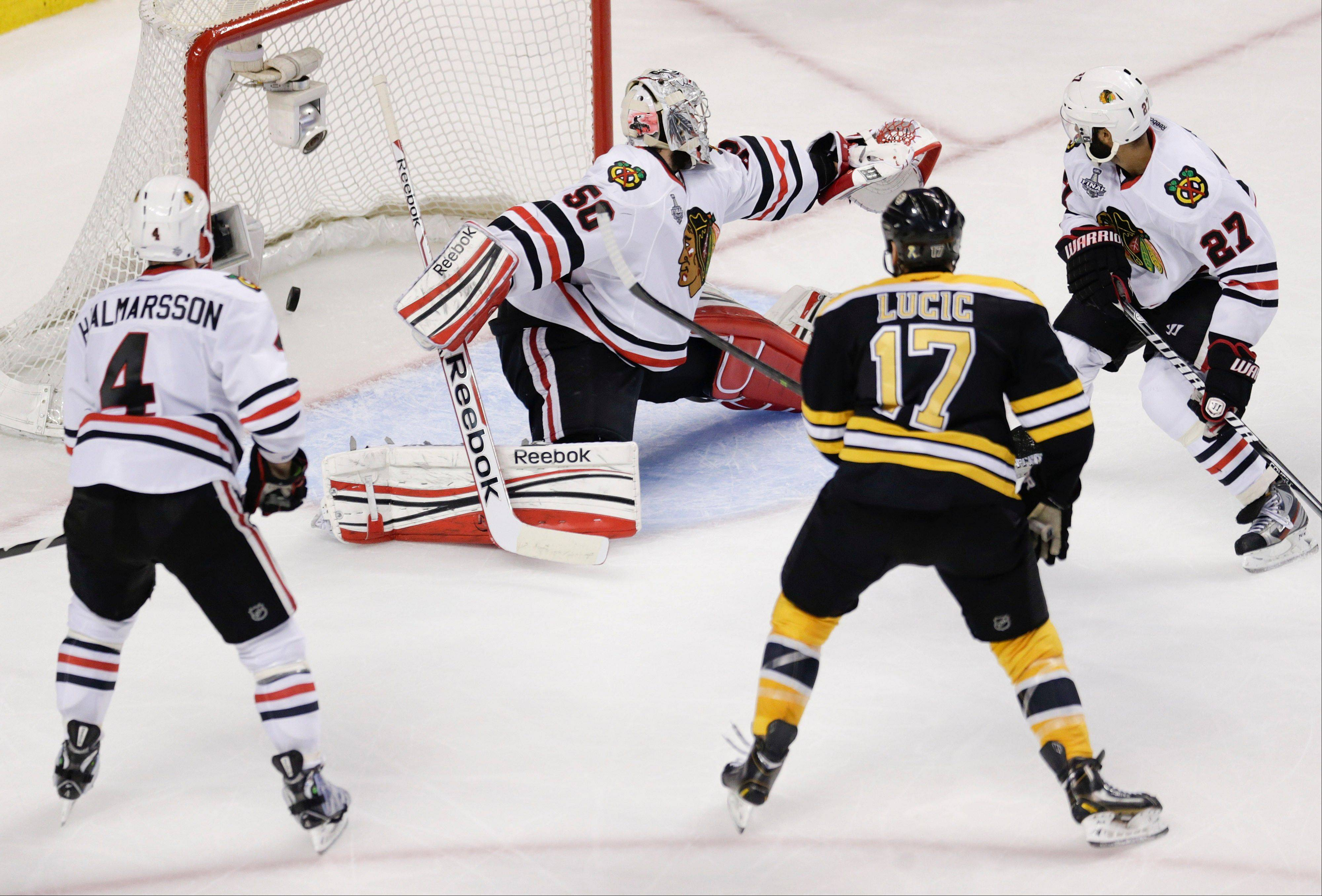 Boston Bruins left wing Milan Lucic (17) scores a goal against Chicago Blackhawks goalie Corey Crawford (50) as defenseman Johnny Oduya (27) and defenseman Niklas Hjalmarsson (4) look on during the second period in Game 4 of the NHL hockey Stanley Cup Finals.
