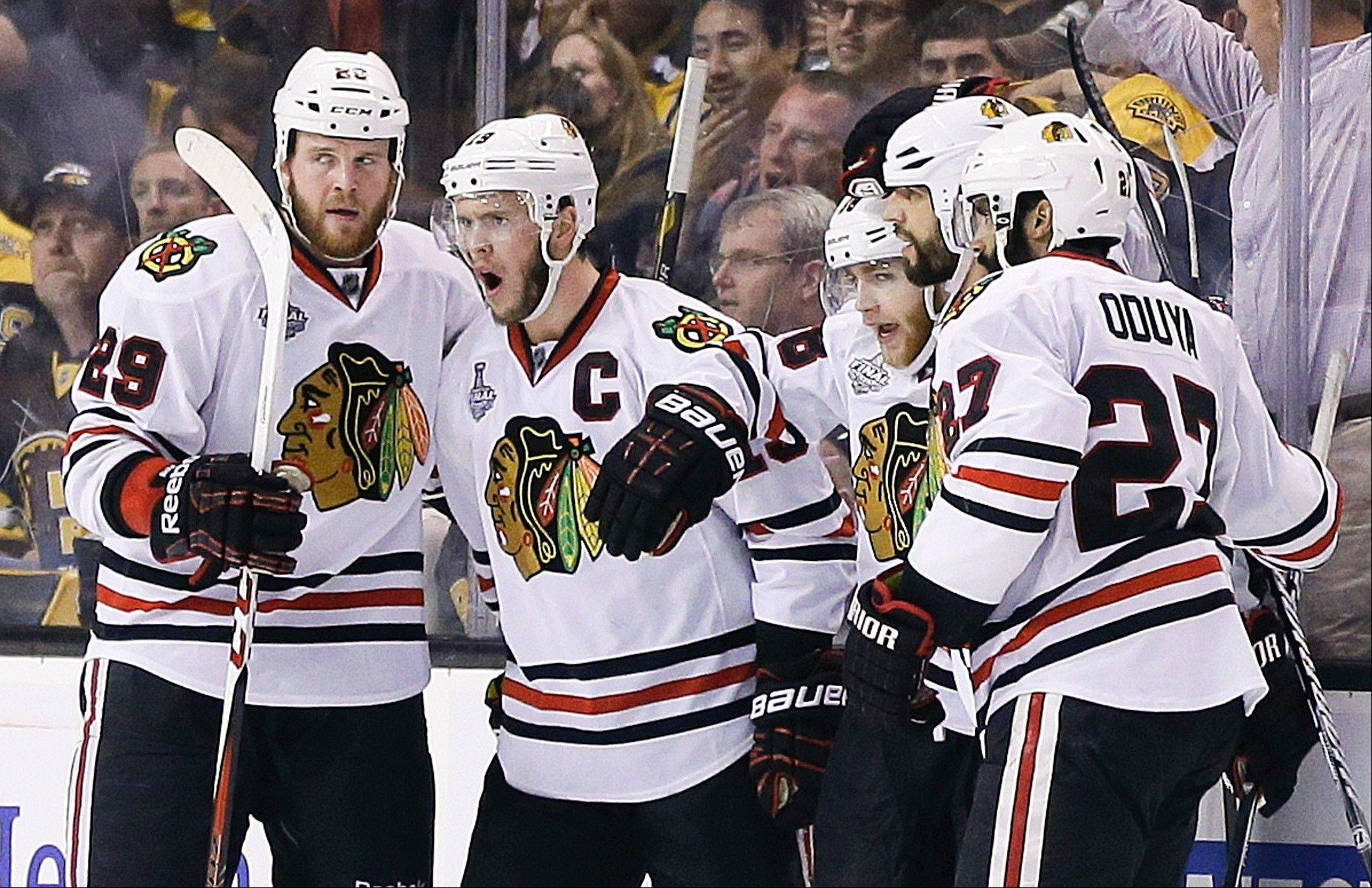 Chicago Blackhawks right wing Patrick Kane, second from right, celebrates his goal against the Boston Bruins with teammates during the second period in Game 4 of the NHL hockey Stanley Cup Finals.