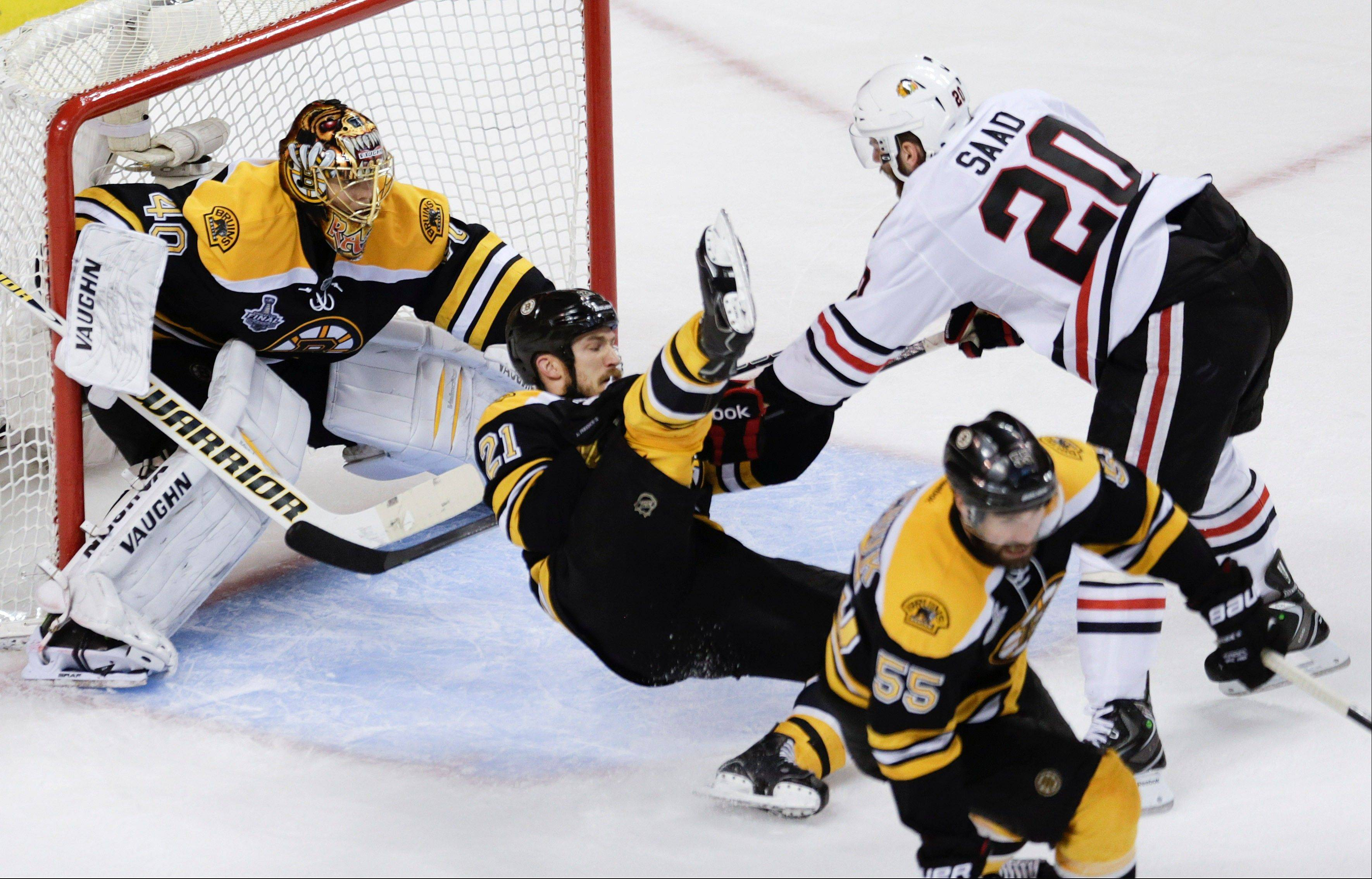 Chicago Blackhawks left wing Brandon Saad (20) takes down Boston Bruins defenseman Andrew Ference (21) in front of Bruins goalie Tuukka Rask (40), of Finland, during the third period in Game 4 of the NHL hockey Stanley Cup Finals.
