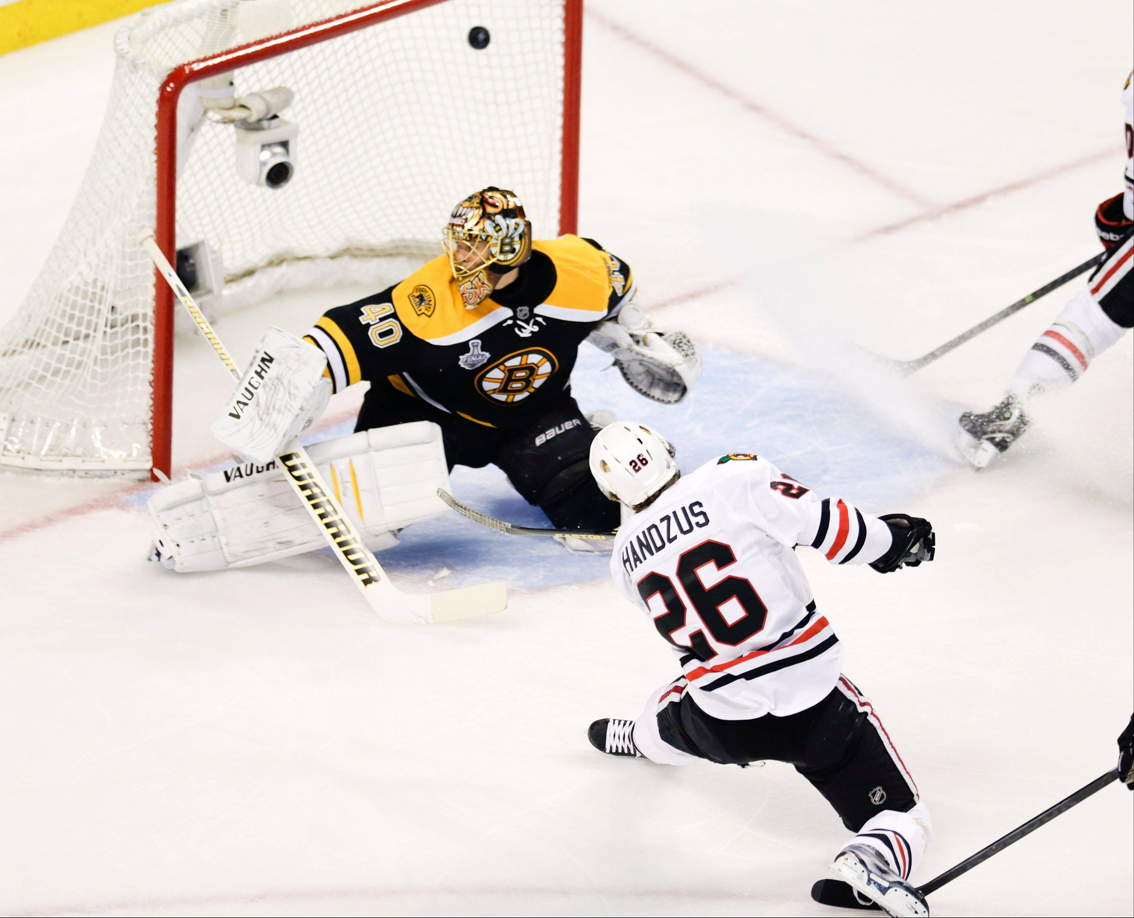Chicago Blackhawks center Michal Handzus (26), of Slovakia, scores past Boston Bruins goalie Tuukka Rask (40), of Finland, during the first period in Game 4 of the NHL hockey Stanley Cup Finals.