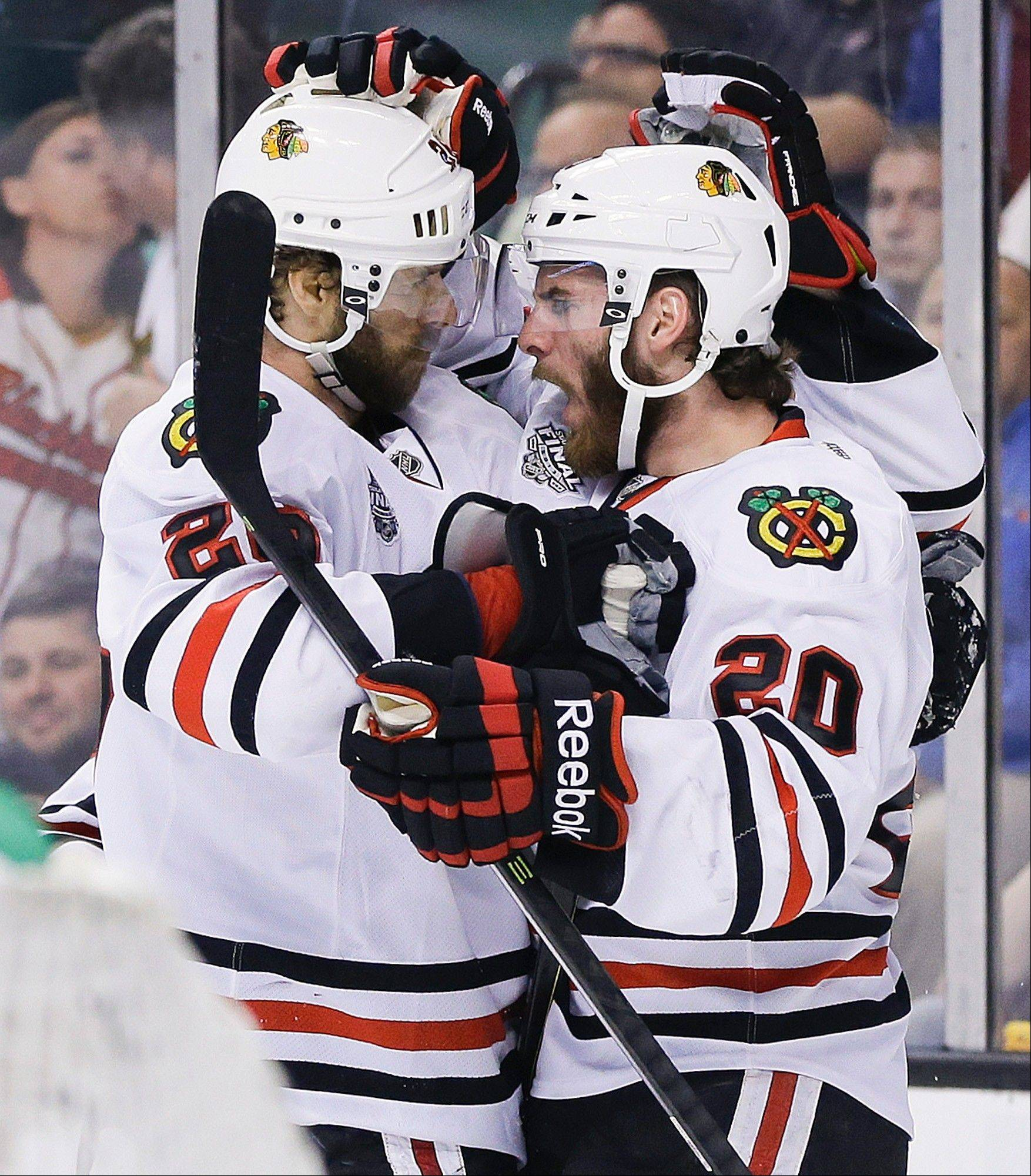 Chicago Blackhawks left wing Brandon Saad (20) congratulates Blackhawks center Michal Handzus, left, of Slovakia, during the first period in Game 4 of the NHL hockey Stanley Cup Finals.
