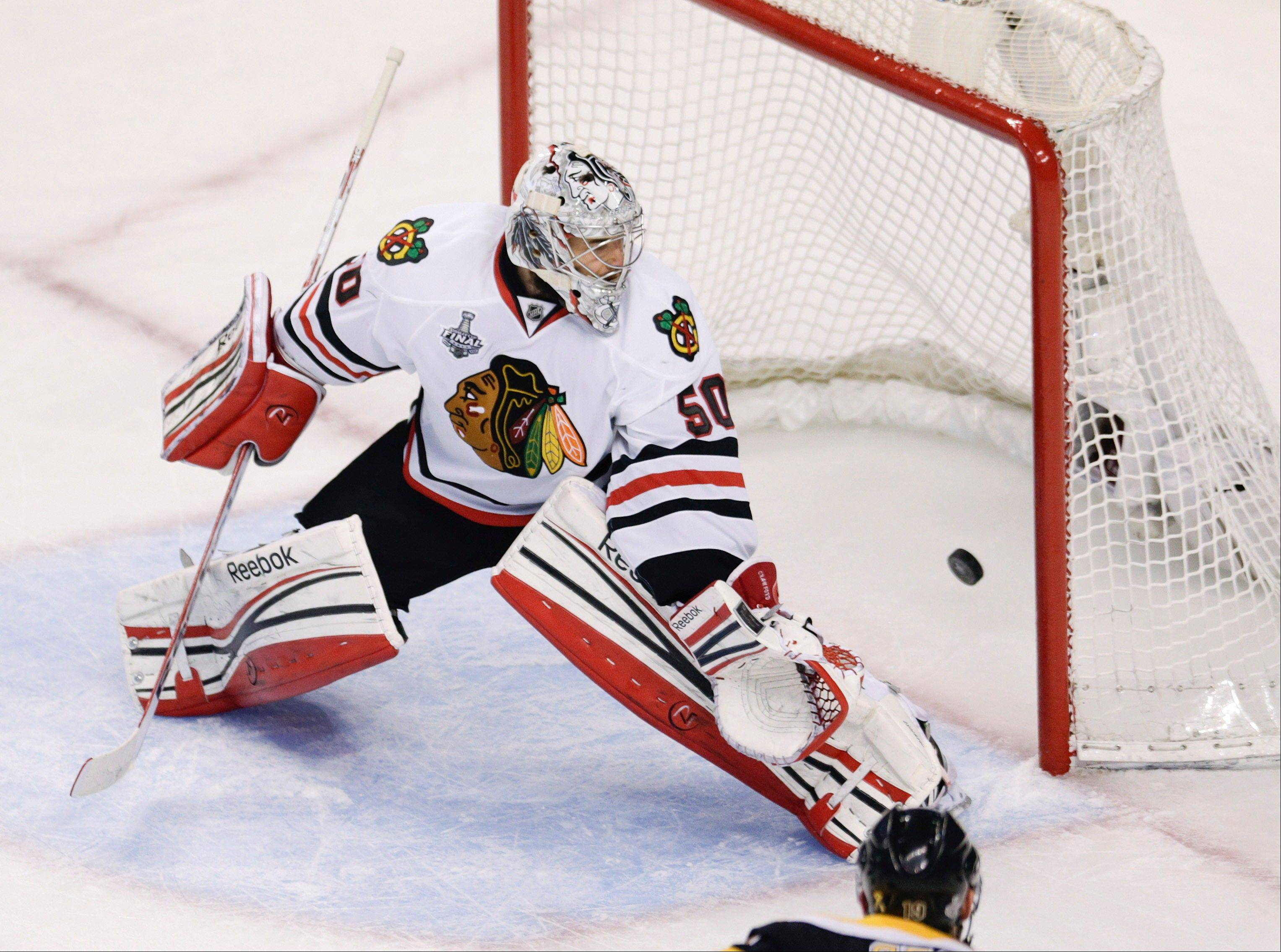 The puck, shot by Boston Bruins center Rich Peverley, not seen, finds the net behind Chicago Blackhawks goalie Corey Crawford (50) for a goal during the first period in Game 4 of the NHL hockey Stanley Cup Finals.