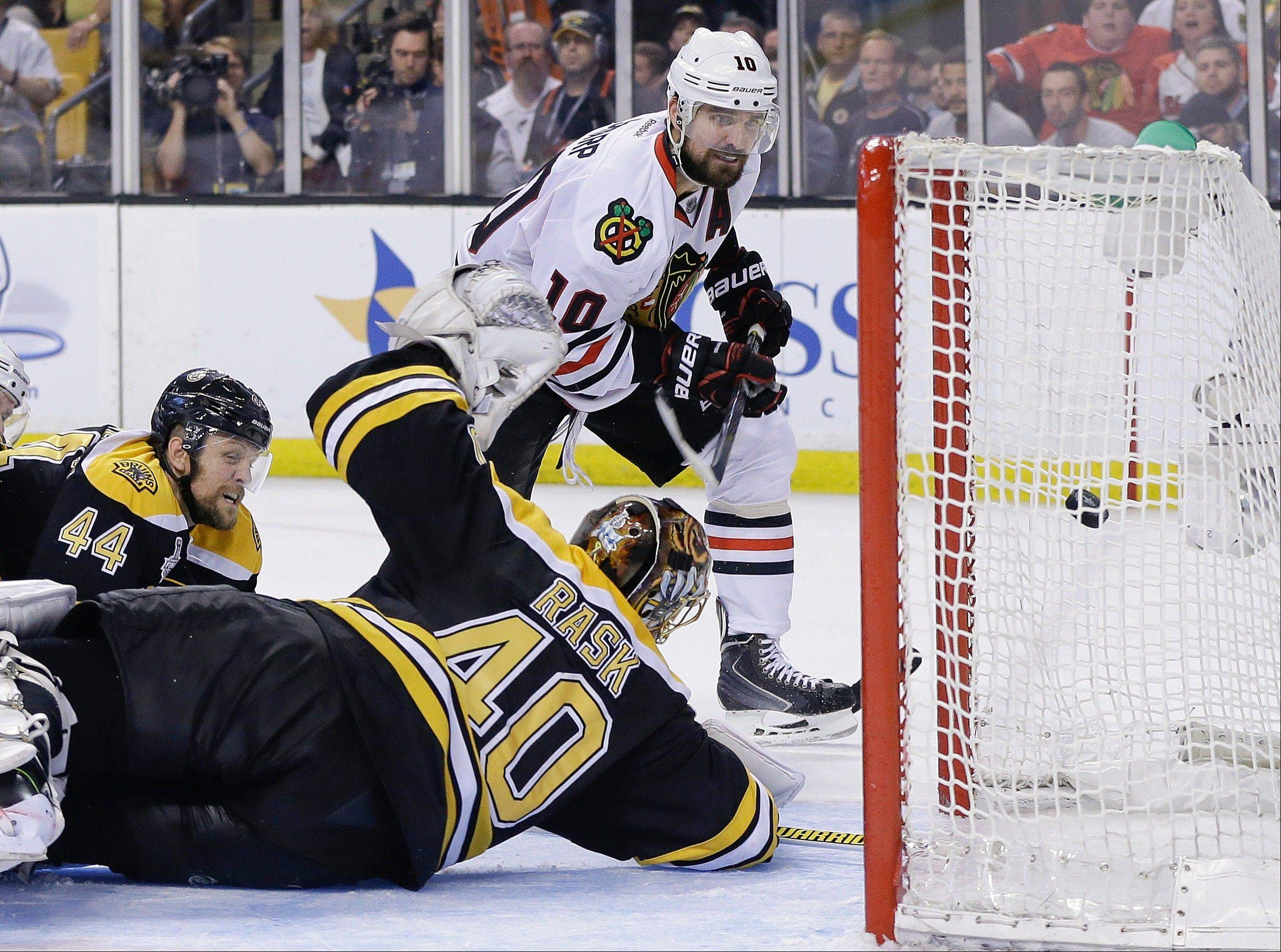 Chicago Blackhawks center Patrick Sharp (10) scores past Boston Bruins goalie Tuukka Rask (40), of Finland, and defenseman Dennis Seidenberg (44), of Germany, during the third period in Game 4 of the NHL hockey Stanley Cup Finals.