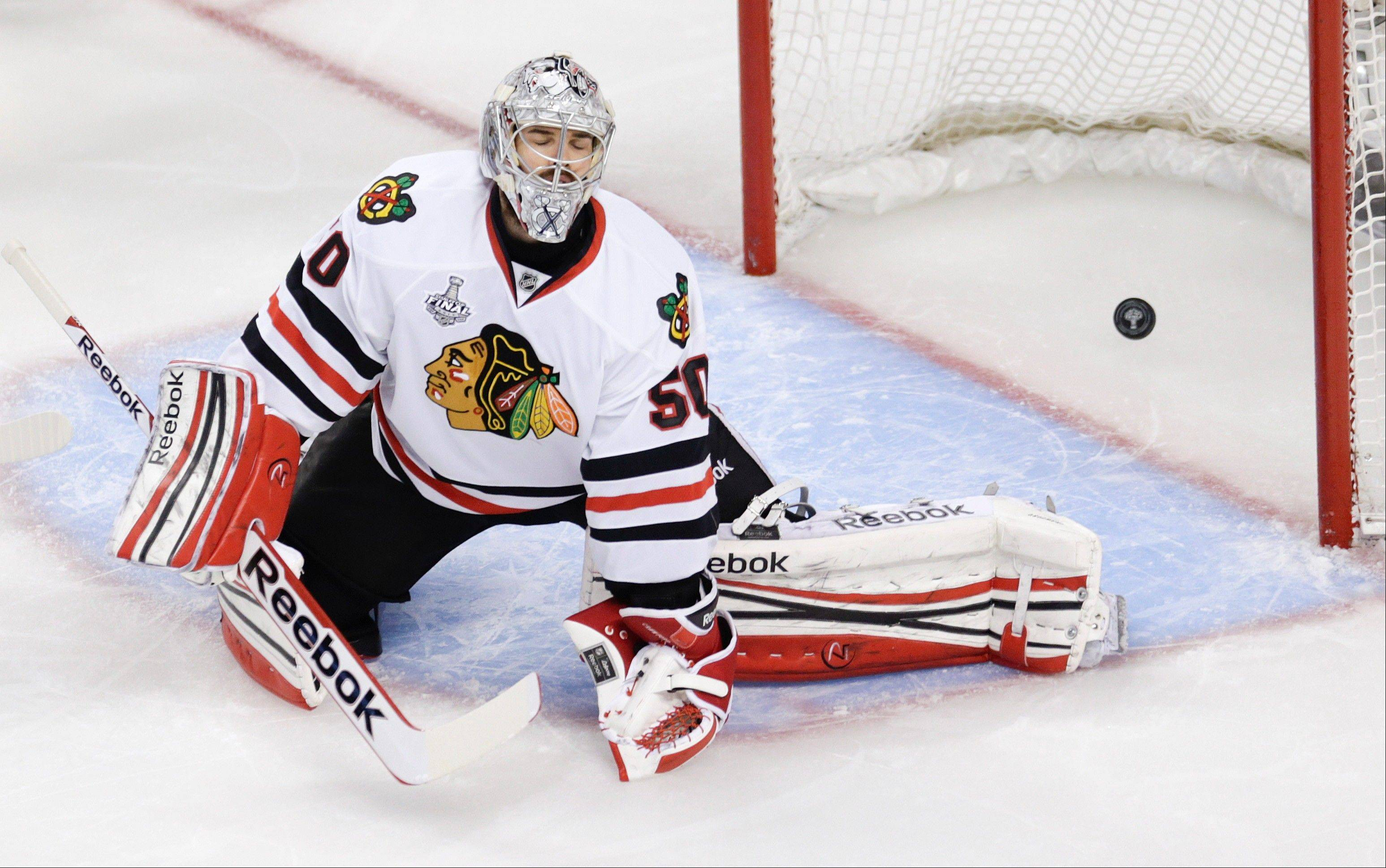 The puck, shot by Boston Bruins center Patrice Bergeron, not seen, sails past Chicago Blackhawks goalie Corey Crawford (50) for a goal during the third period in Game 4 of the NHL hockey Stanley Cup Finals.