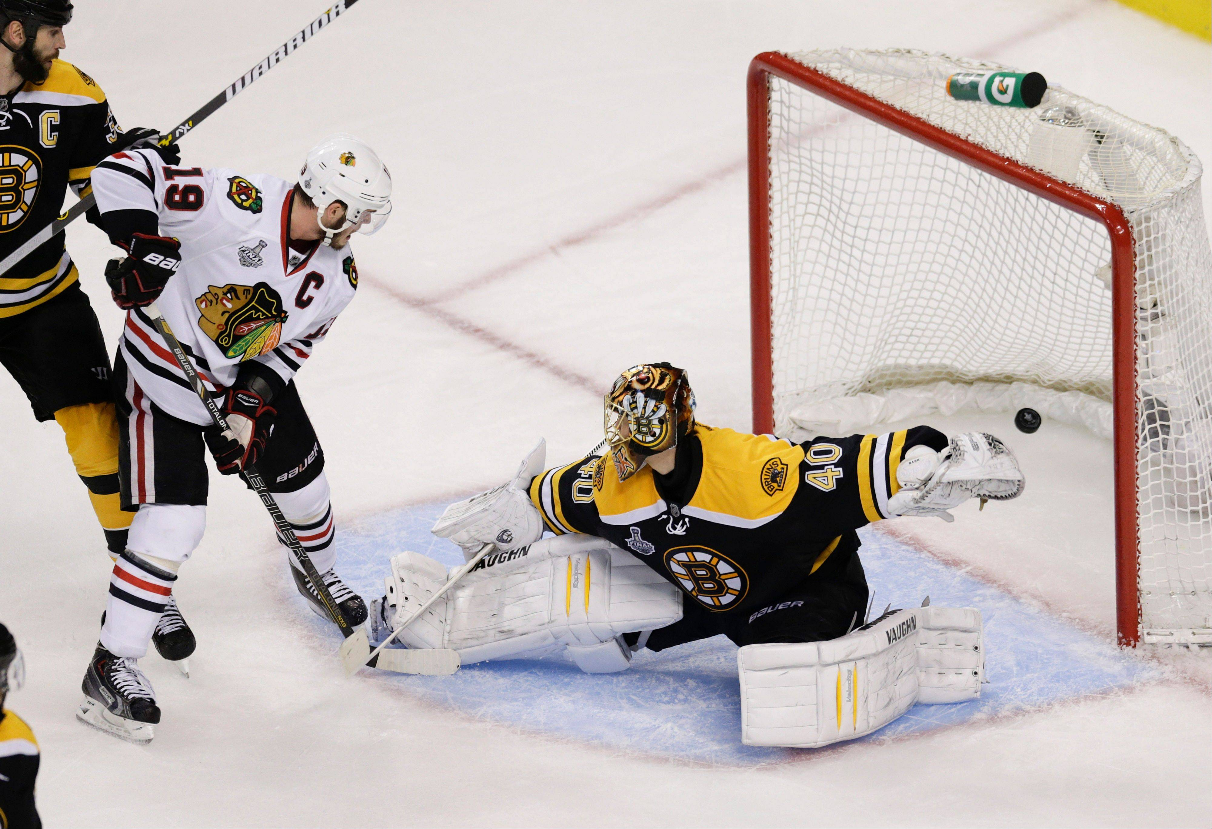 Chicago Blackhawks center Jonathan Toews (19) watches the winning goal by teammate Brent Seabrook, not shown, sail past Boston Bruins goalie Tuukka Rask (40), of Finland, during the first overtime period in Game 4 of the NHL hockey Stanley Cup Finals.