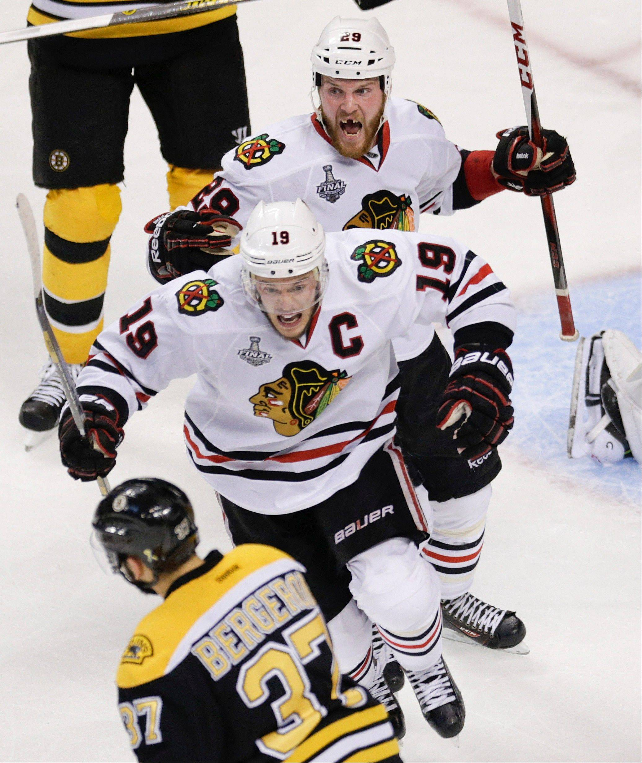 Chicago Blackhawks left wing Bryan Bickell (29) and center Jonathan Toews (19) celebrate the winning goal by Brent Seabrook, not shown, in front of Boston Bruins center Patrice Bergeron (37) during the first overtime period in Game 4 of the NHL hockey Stanley Cup Finals.
