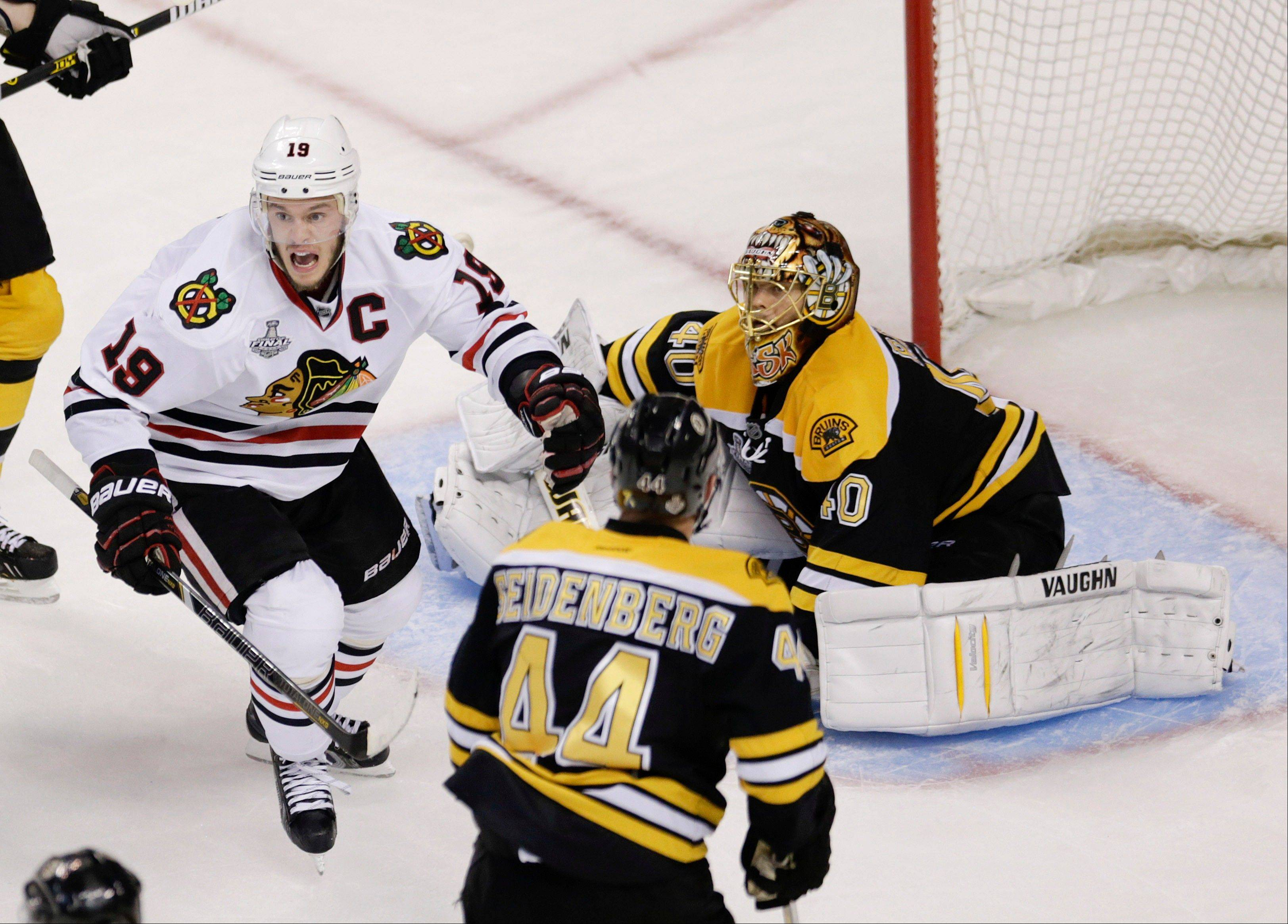 Chicago Blackhawks center Jonathan Toews (19) celebrates the winning goal by Brent Seabrook, not shown, against Boston Bruins goalie Tuukka Rask (40), of Finland, during the first overtime period in Game 4 of the NHL hockey Stanley Cup Finals.
