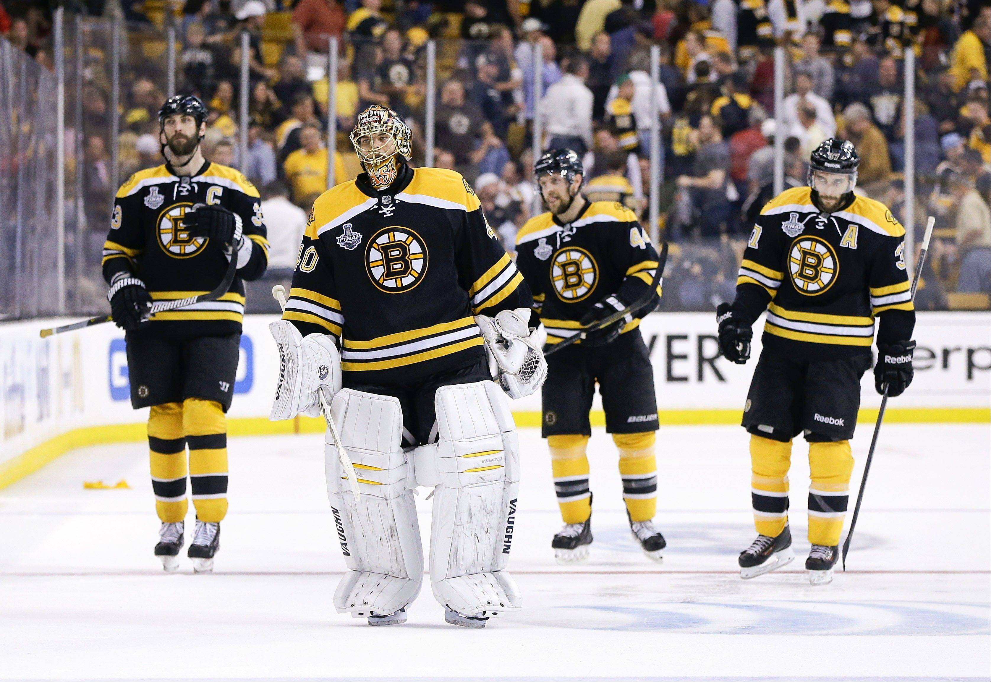 Boston Bruins defenseman Zdeno Chara (33), of Slovakia, Boston Bruins goalie Tuukka Rask (40), of Finland, Boston Bruins defenseman Dennis Seidenberg (44), of Germany, and Boston Bruins center Patrice Bergeron (37) leave the ice after their 6-5 loss to the Chicago Blackhawks during the first overtime period in Game 4 of the NHL hockey Stanley Cup Finals.