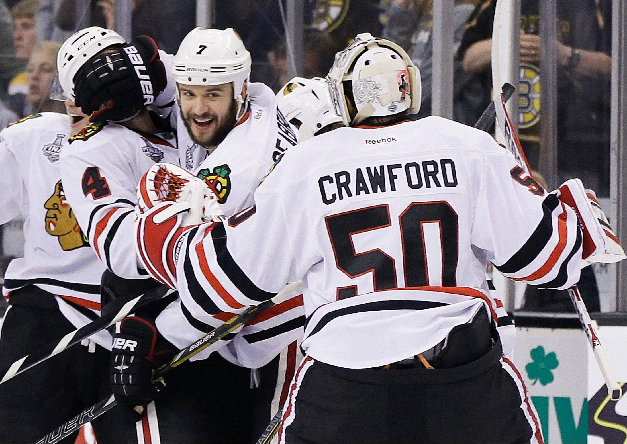 Chicago Blackhawks defenseman Brent Seabrook (7) celebrates his game-winning goal against the Boston Bruins with Chicago Blackhawks goalie Corey Crawford (50) during the first overtime period in Game 4 of the NHL hockey Stanley Cup Finals.