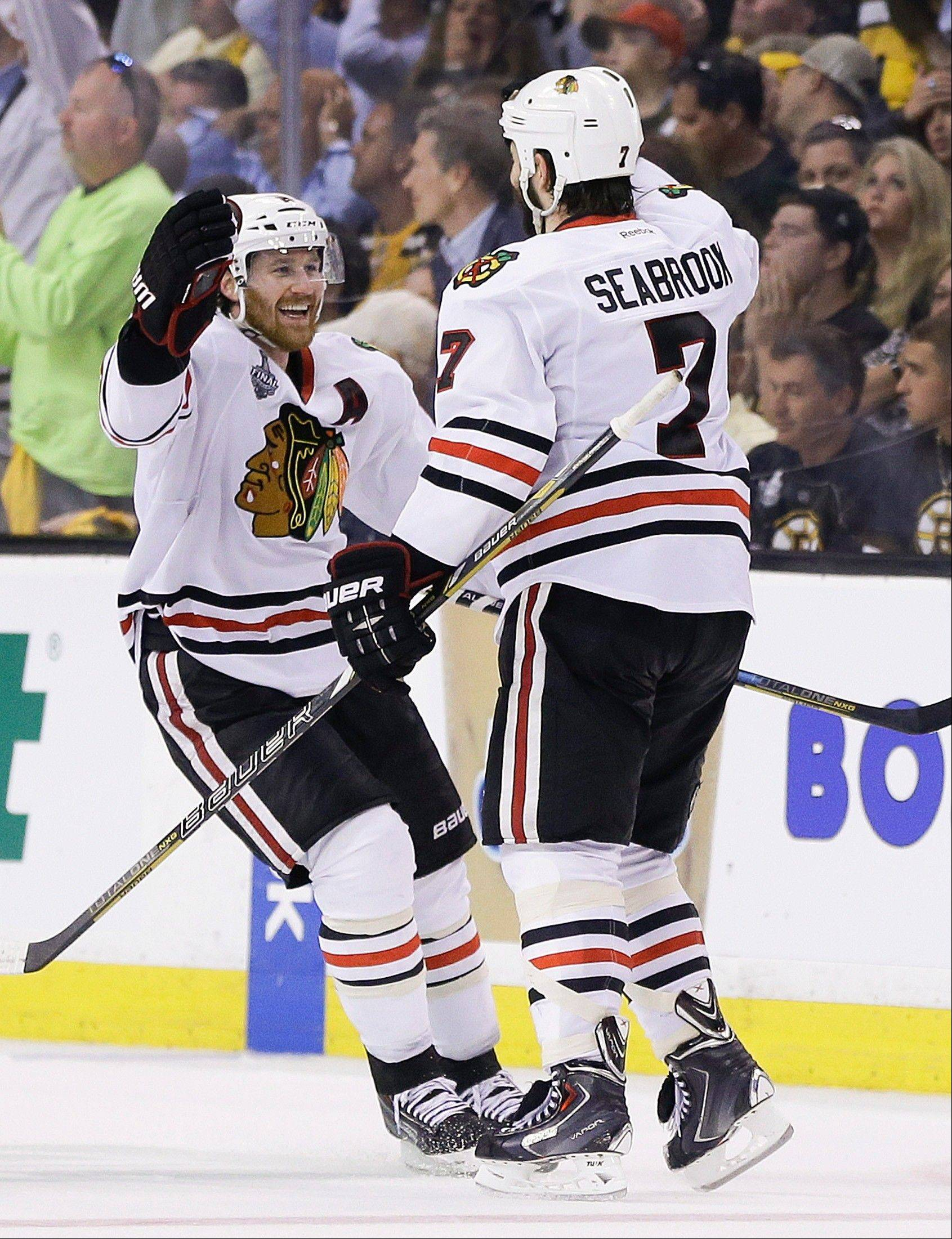 Chicago Blackhawks defenseman Brent Seabrook (7) celebrates his game-winning goal against the Boston Bruins with defenseman Duncan Keith (2) during the first overtime period in Game 4 of the NHL hockey Stanley Cup Finals, Chicago won 6-5 in overtime.