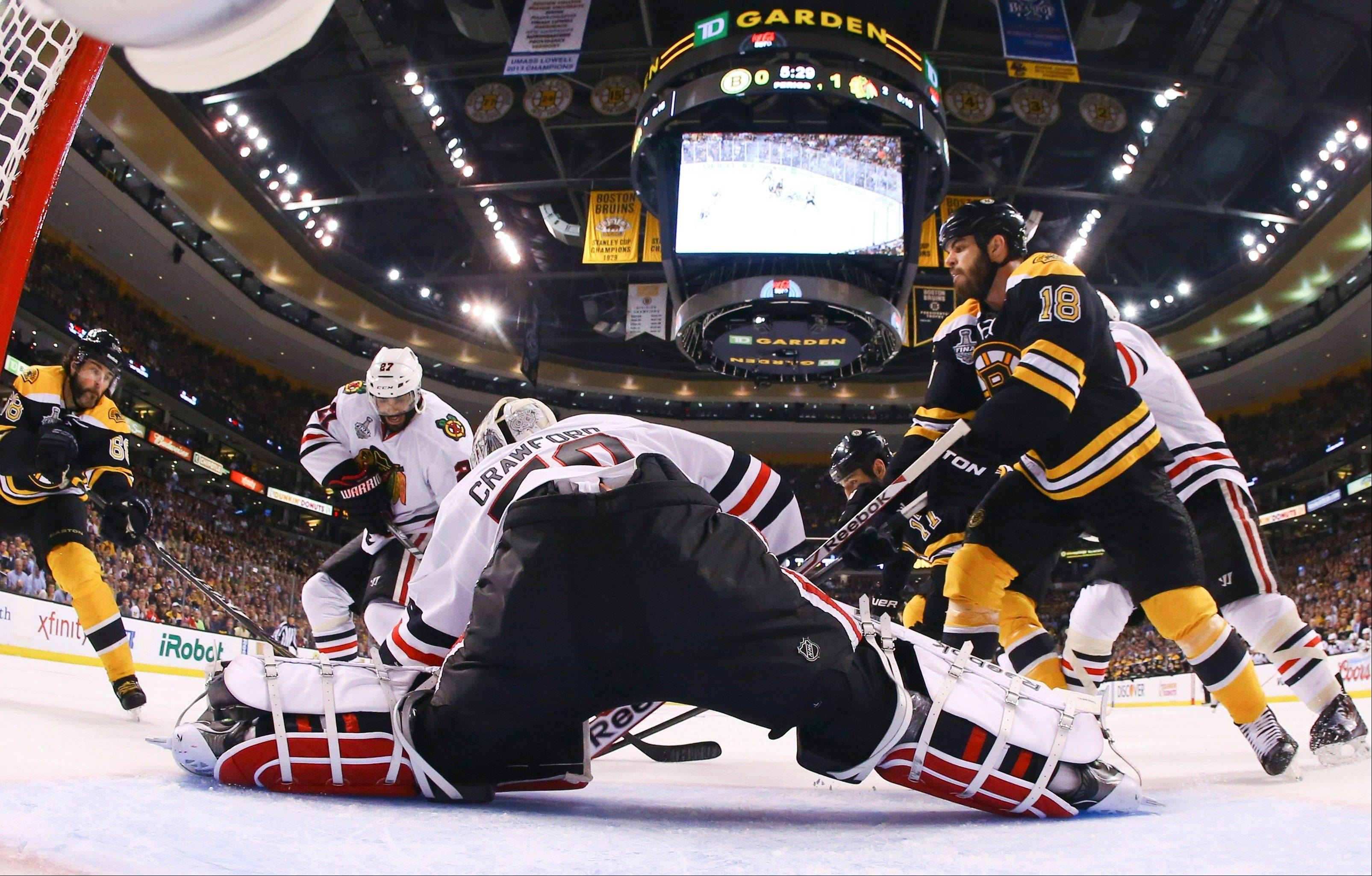 Chicago Blackhawks goalie Corey Crawford (50) defends the net against Boston Bruins right wing Jaromir Jagr (68), of the Czech Republic, and Bruins right wing Nathan Horton (18) during the first period in Game 4 of the NHL hockey Stanley Cup Finals Wednesday, June 19, 2013, in Boston. (AP Photo/Harry How, Pool)