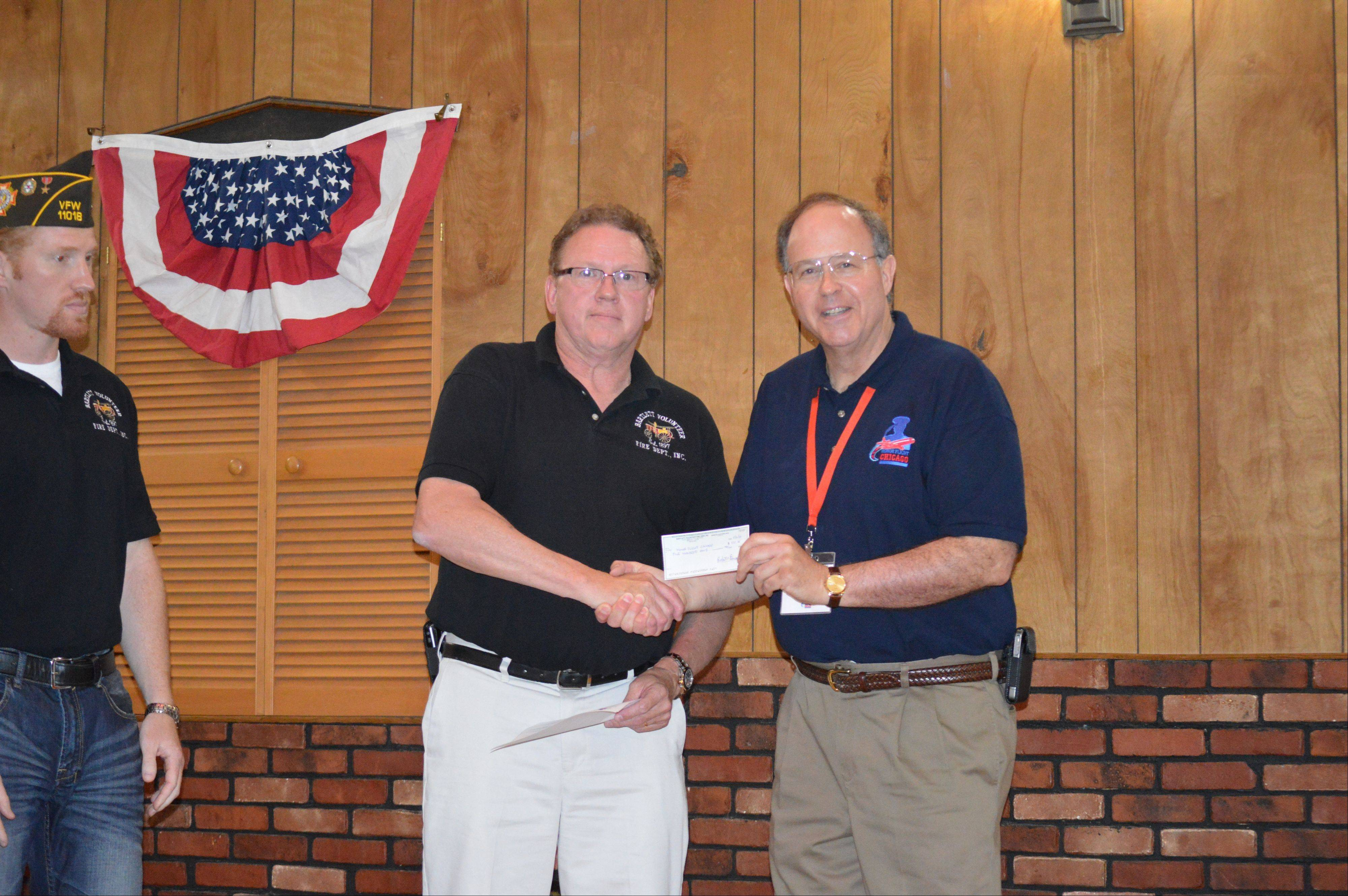 Bartlett Volunteer Fire Association President Mike Dexter presents a donation to Ron Wolflick and Honor Flight Chicago.