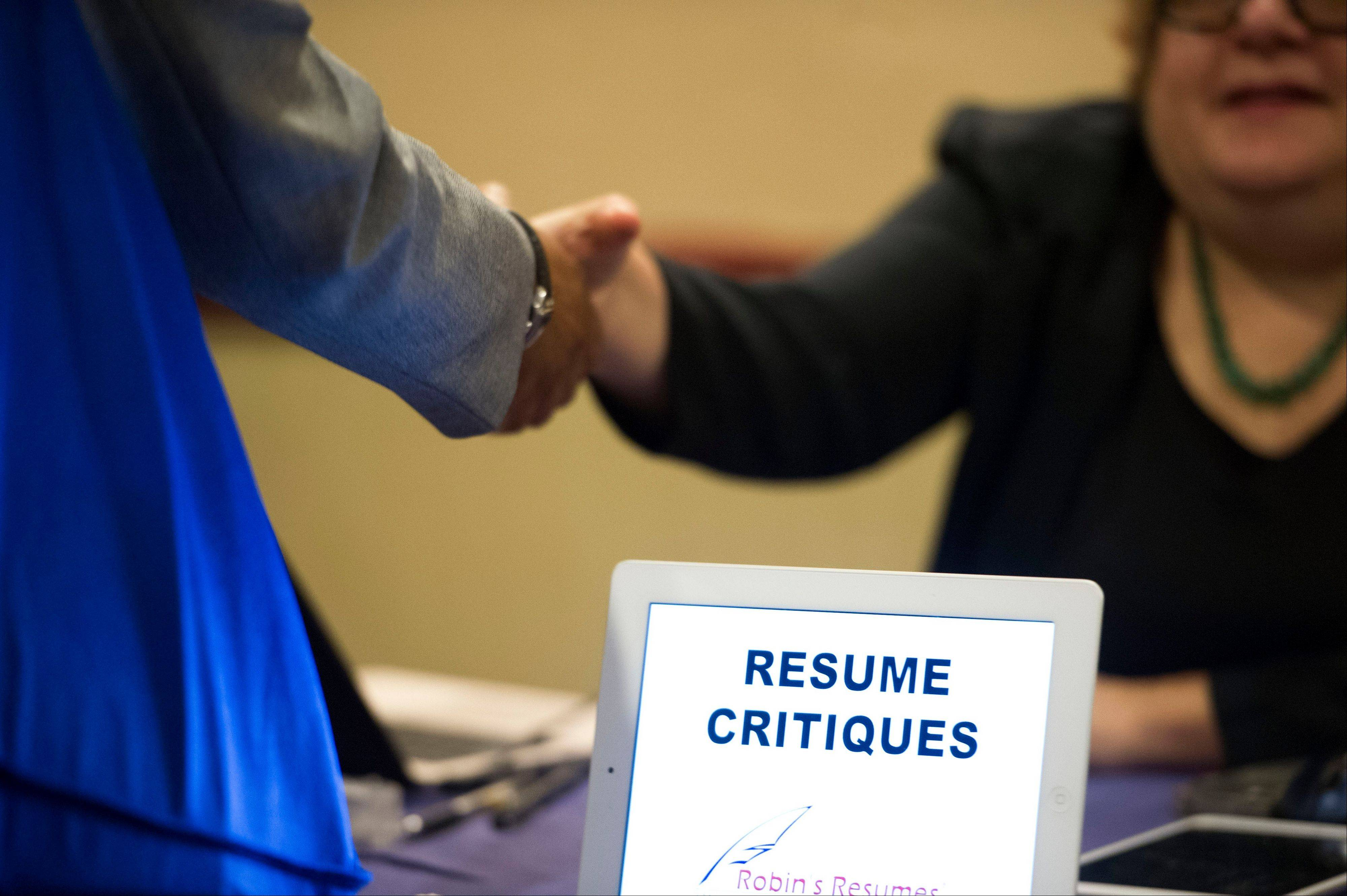 A job seeker stops at a table offering resume critiques during a job fair held in Atlanta. Applications for U.S. unemployment benefits rose by 18,000 last week to a seasonally adjusted 354,000. Despite the gain, the level remains consistent with moderate job growth.