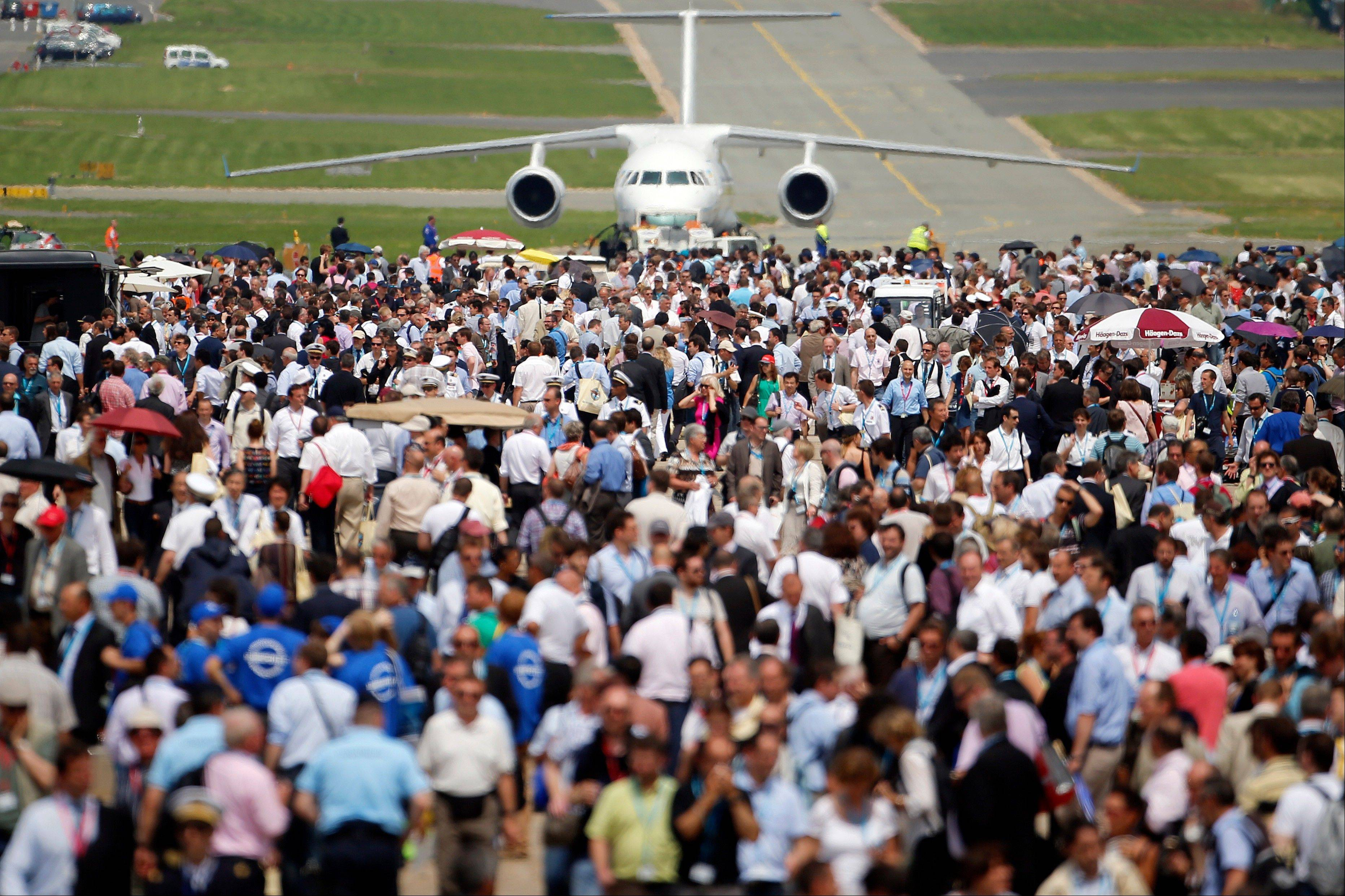 Visitors walk by a Russian Antonov 58, in the background, during the 50th Paris Air Show at Le Bourget airport, north of Paris, Wednesday, June 19, 2013. (AP Photo/Francois Mori)